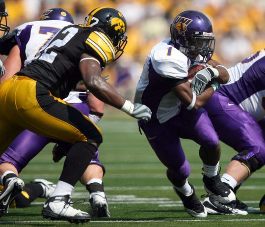 Northern Iowa running back Carlos Anderson (1) looks for running room Sept. 5, 2009 as Iowa linebacker Jeremiha Hunter approaches in Iowa City.