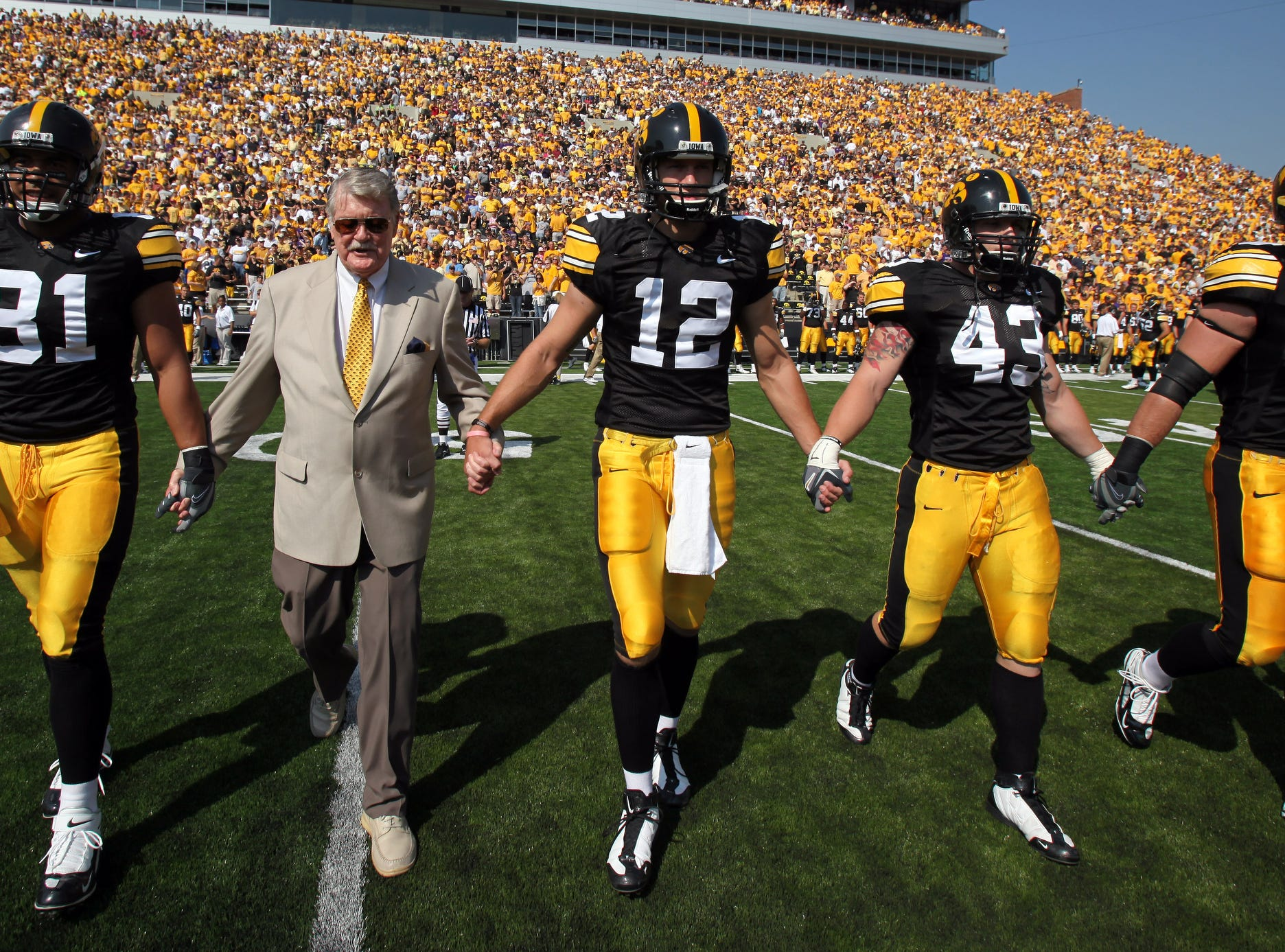 Former Iowa football coach Hayden Fry walks as an honorary captain with players Tony Moeaki (81), Ricky Stanzi (12), Pat Angerer (43) and A.J. Edds (49) before kickoff Sept. 5, 2009 in Iowa City.