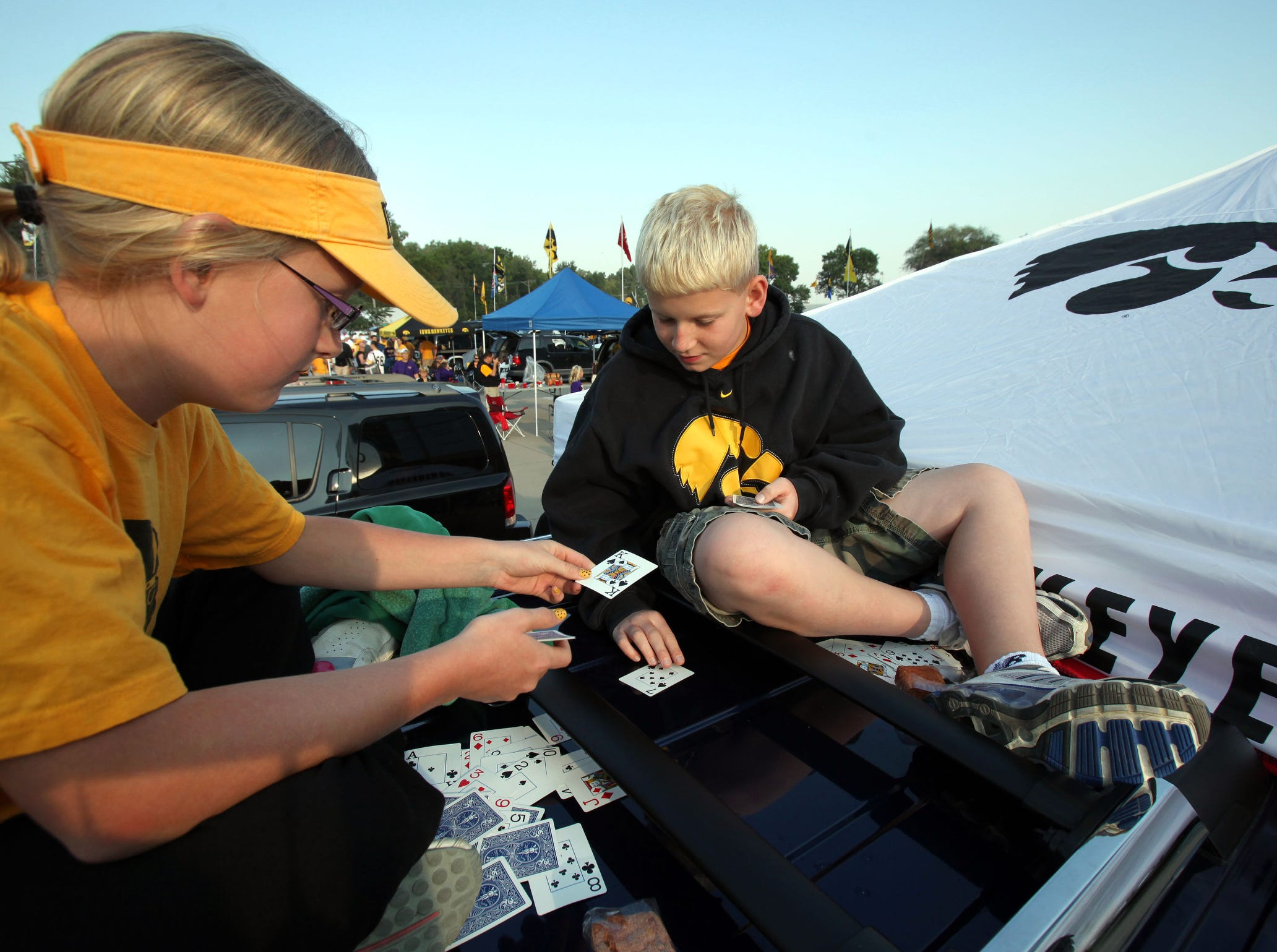Twins Ally and Isaac Davis of Mount Pleasant play cards atop a truck while tailgating before Iowa's football season opener against Northern Iowa on Sept. 5, 2009 in Iowa City.
