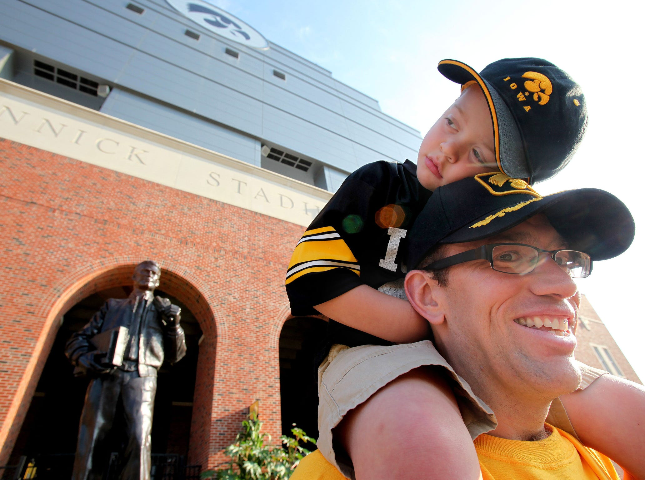 Iowa medical school graduate Mark Reese of Fort Collins, Colorado, gives his son, Caden, 4, a high perch outside Kinnick Stadium before Iowa's football season opener Sept. 5, 2009 against Northern Iowa  in Iowa City.