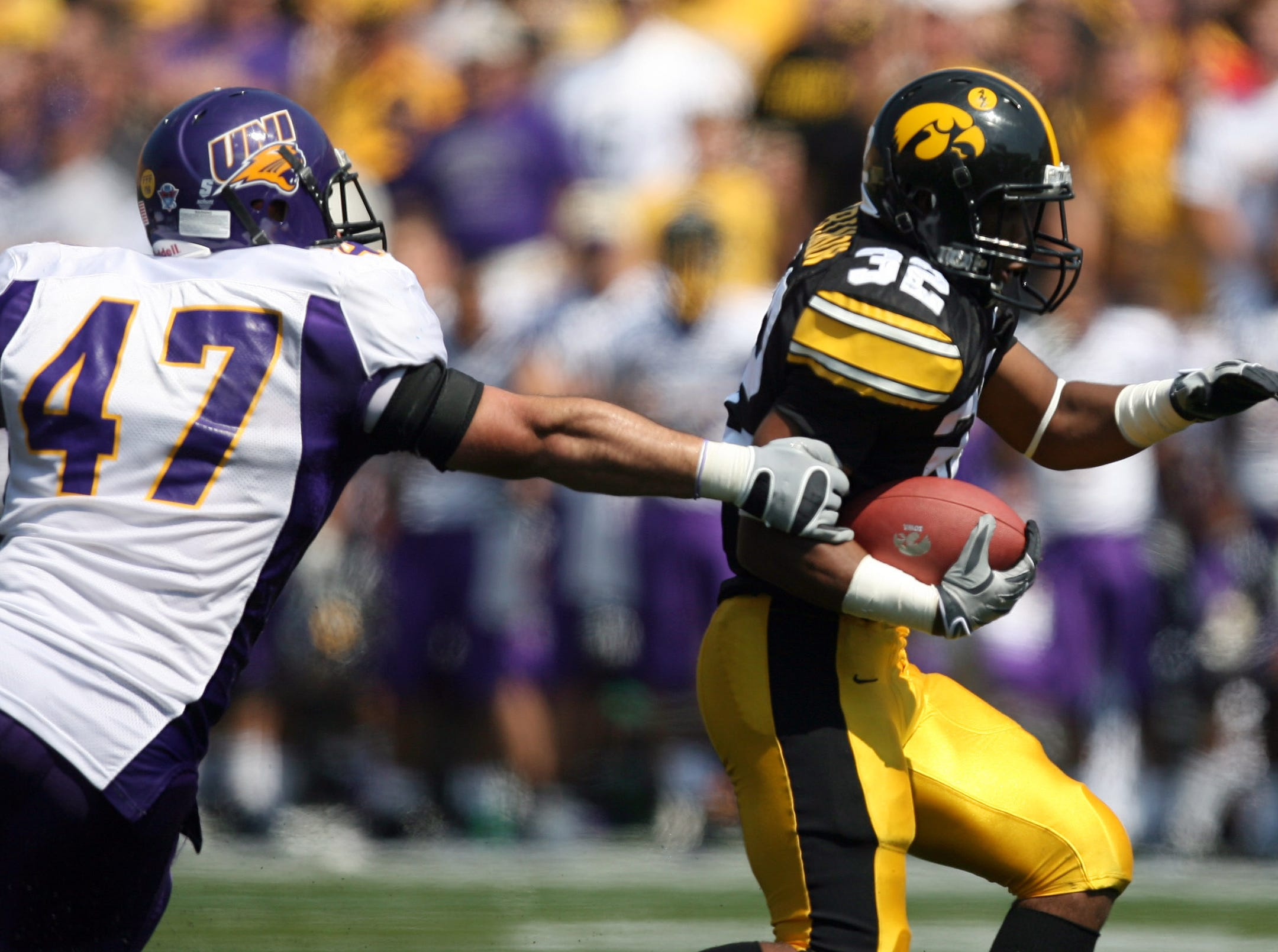 s0906iowafb - shot 09/05/09 Iowa City, IA.  Christopher Gannon/The Register  -- Iowa vs. Northern Iowa --   Iowa running back Adam Robinson (32) gets past past Northern Iowa linebacker Josh Mahoney (47) Saturday in Iowa City.  (Christopher Gannon/The Des Moines Register)