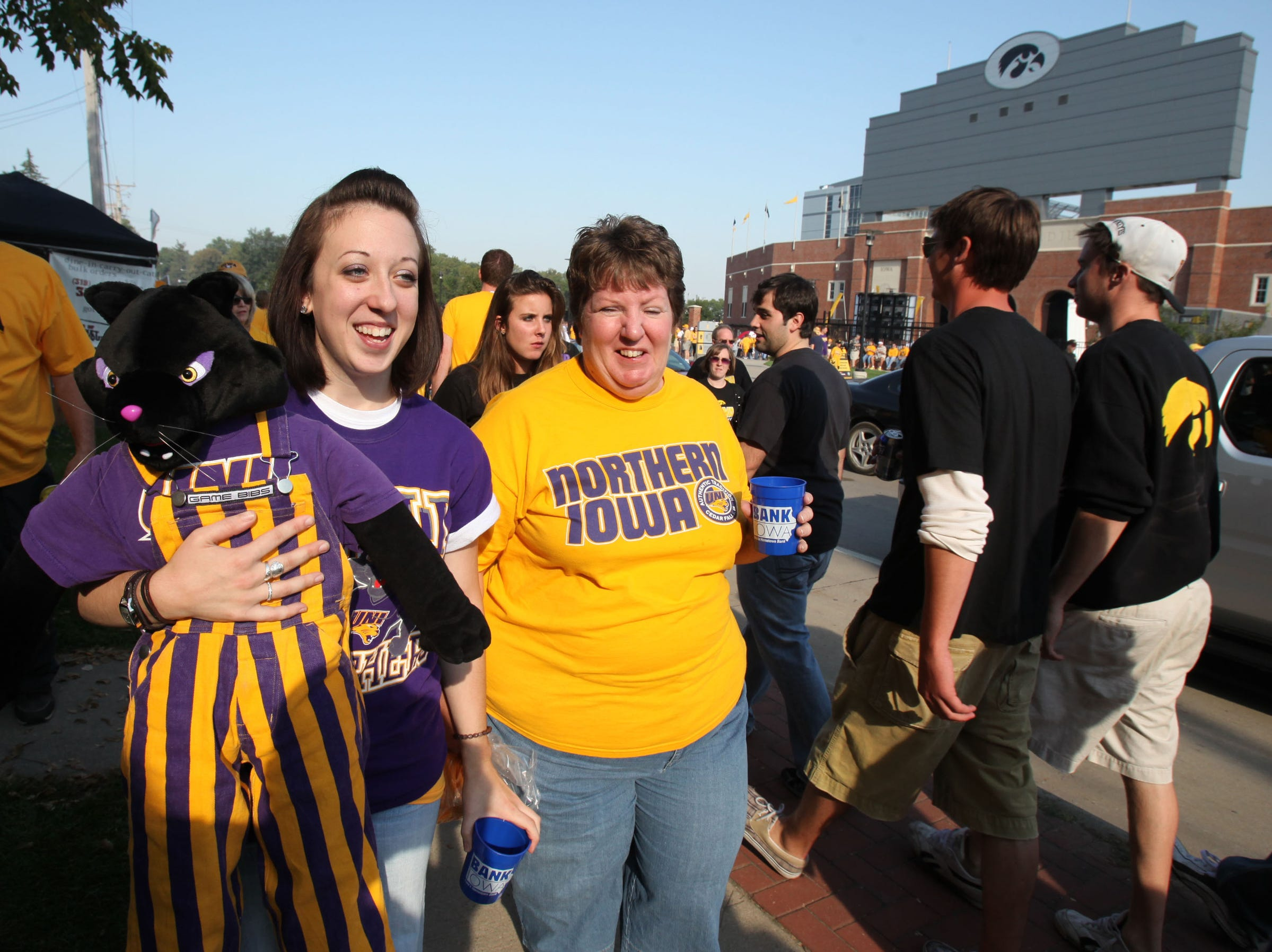 Northern Iowa senior Courtney Janaszak, left, of Cedar Falls, carries a panther mascot with her mother, Terri,  before Iowa's football season opener against Northern Iowa on Sept. 5, 2009 in Iowa City.