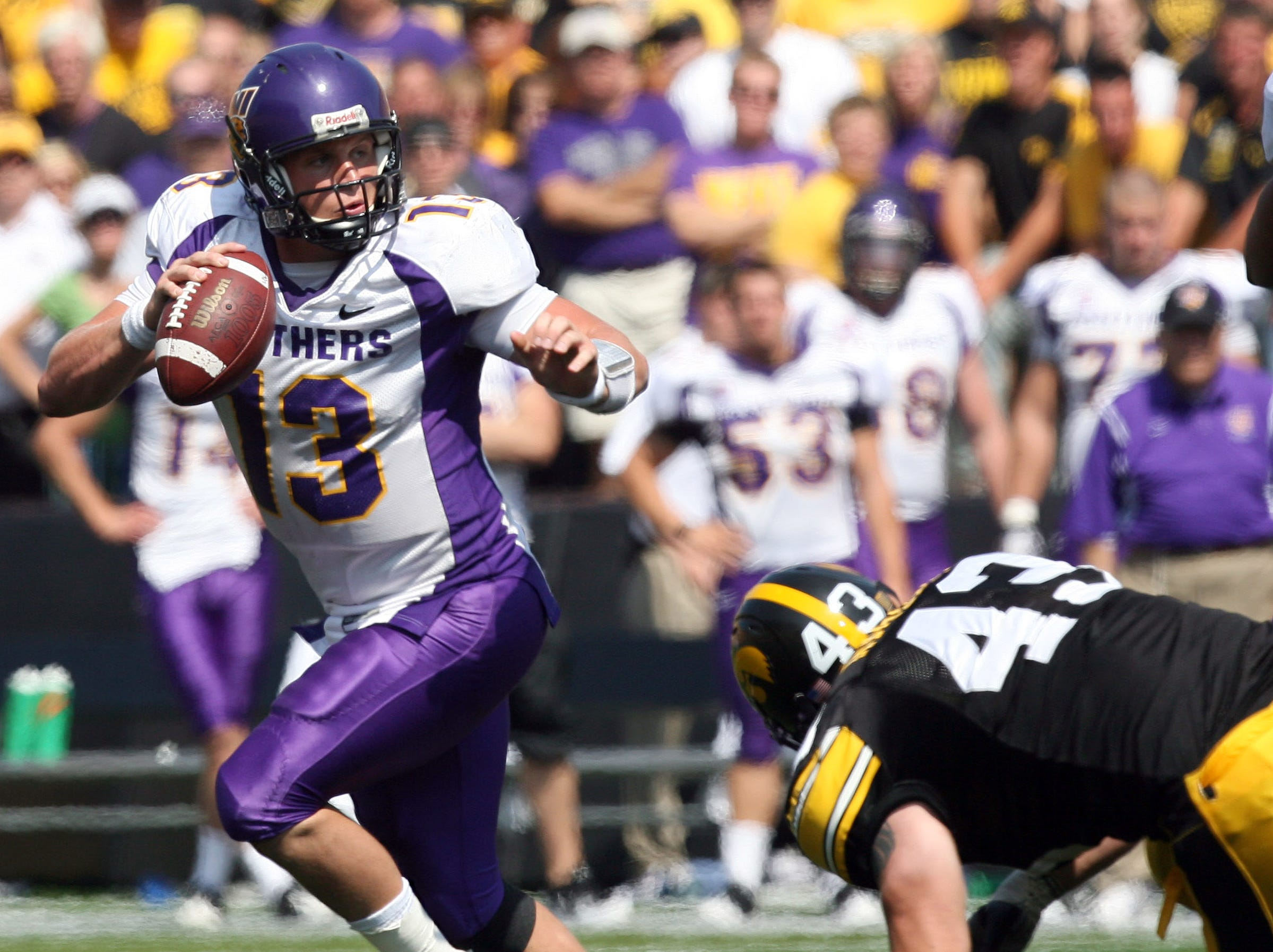 s0906iowafb - shot 09/05/09 Iowa City, IA.  Christopher Gannon/The Register  -- Iowa vs. Northern Iowa --   Northern Iowa quarterback Pat Grace (13) eludes Iowa linebacker Pat Angerer (43) while running out of the pocket Saturday in Iowa City.  (Christopher Gannon/The Des Moines Register)