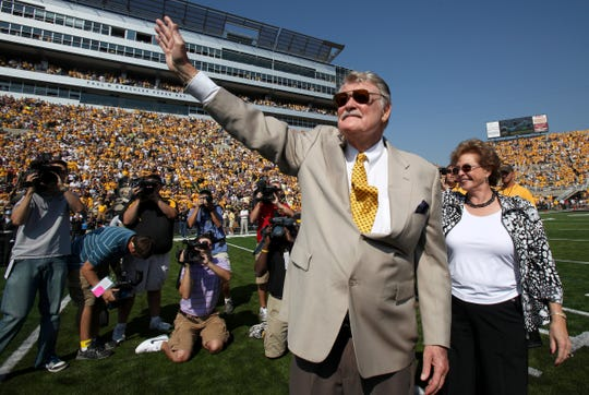 Former Iowa coach Hayden Fry, who passed away recently, waves to the Kinnick Stadium crowd in 2009.