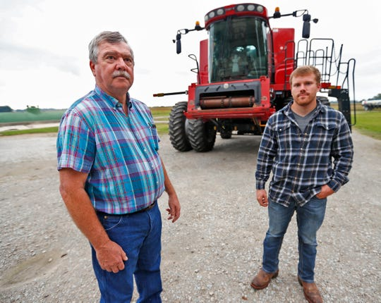 Jud Vaught, left, and Luke Dougherty stand by the combine on Vaught's farm in Franklin, Wednesday, Sept. 12, 2018.  Vaught is soon to retire and will be renting his land to Dougherty to farm.  Vaught is concerned about how tariffs will affect the value of the land.