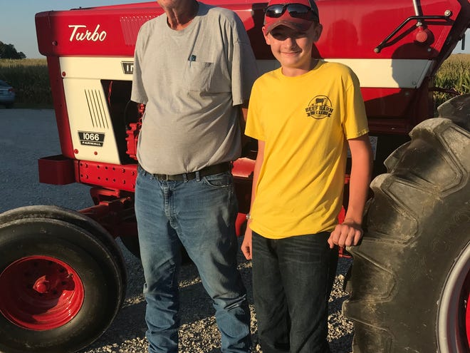 Fred Cox on his farm 5 miles north of Greencastle, with one of his two grandsons, Zach Purdue. Zach, 14, is a freshman at North Putnam. The tractor is his -- he's following in his grandad's footsteps.