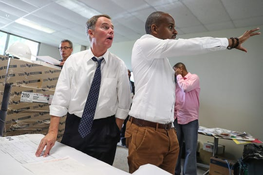 Mayor Hogsett and Douglas Morris compare a blueprint to their surrounding while touring the future Best Buy Teen Tech Center at the Martin Luther King Community Center.