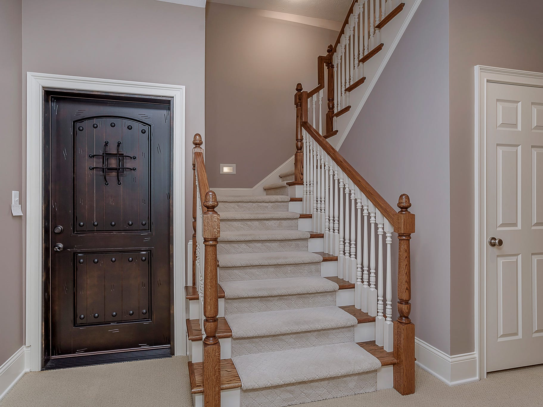 Staircase leading to the basement with view of door to wine cellar.