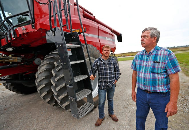 Luke Dougherty, left, and Jud Vaught stand by the combine on Vaught's farm in Franklin, Wednesday, Sept. 12, 2018.  Vaught is soon to retire and will be renting his land to Dougherty to farm.  Vaught is concerned about how tariffs will affect the value of the land.