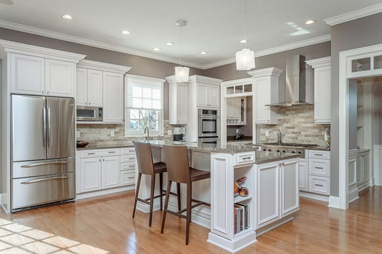 The kitchen features a center island with breakfast bar, granite counter tops, butler's pantry and stainless steel appliances.