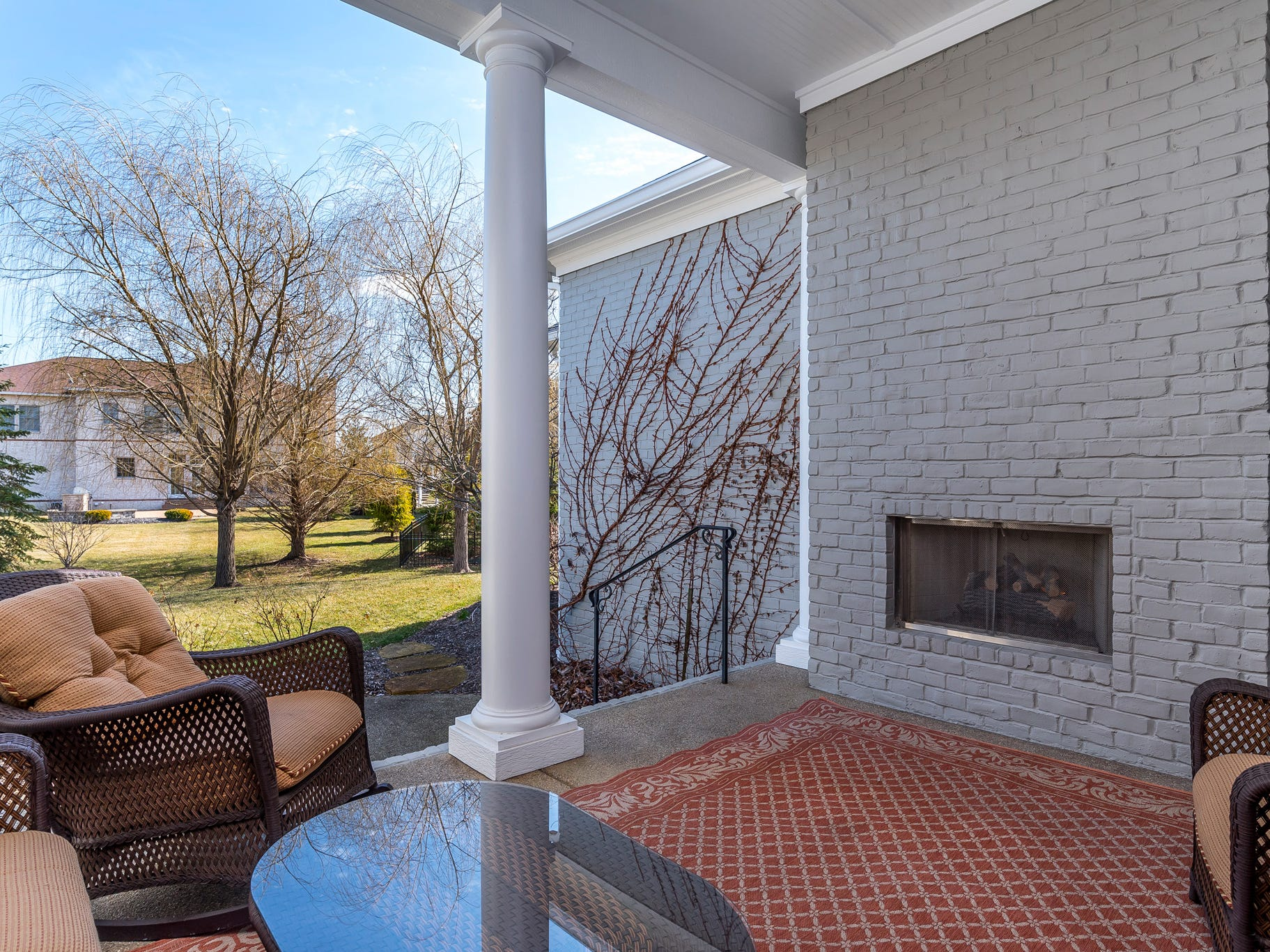 Covered back patio features a fireplace.