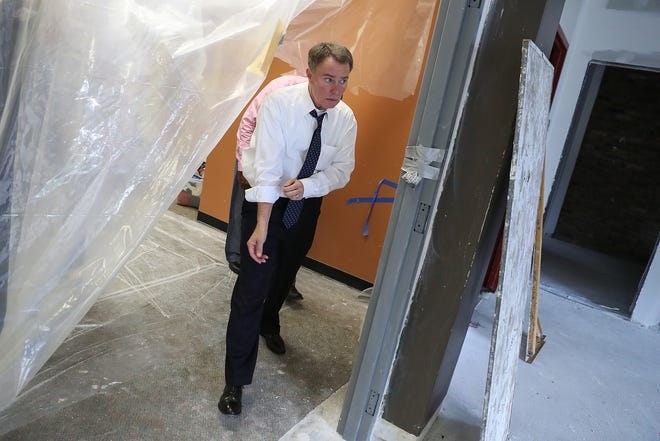 Indianapolis Mayor Joe Hogsett rolls up his sleeves as he tours renovations at the Martin Luther King Community Center in Indianapolis, Tuesday, Sept. 11, 2018. The center is one of five recipients of the city's first community-based violence prevention partnership grants awarded by Hogsett in August. The grant will help operate the mid-construction Best Buy Teen Tech Center, a state-of-the-art technology hub for neighborhood children and teens.