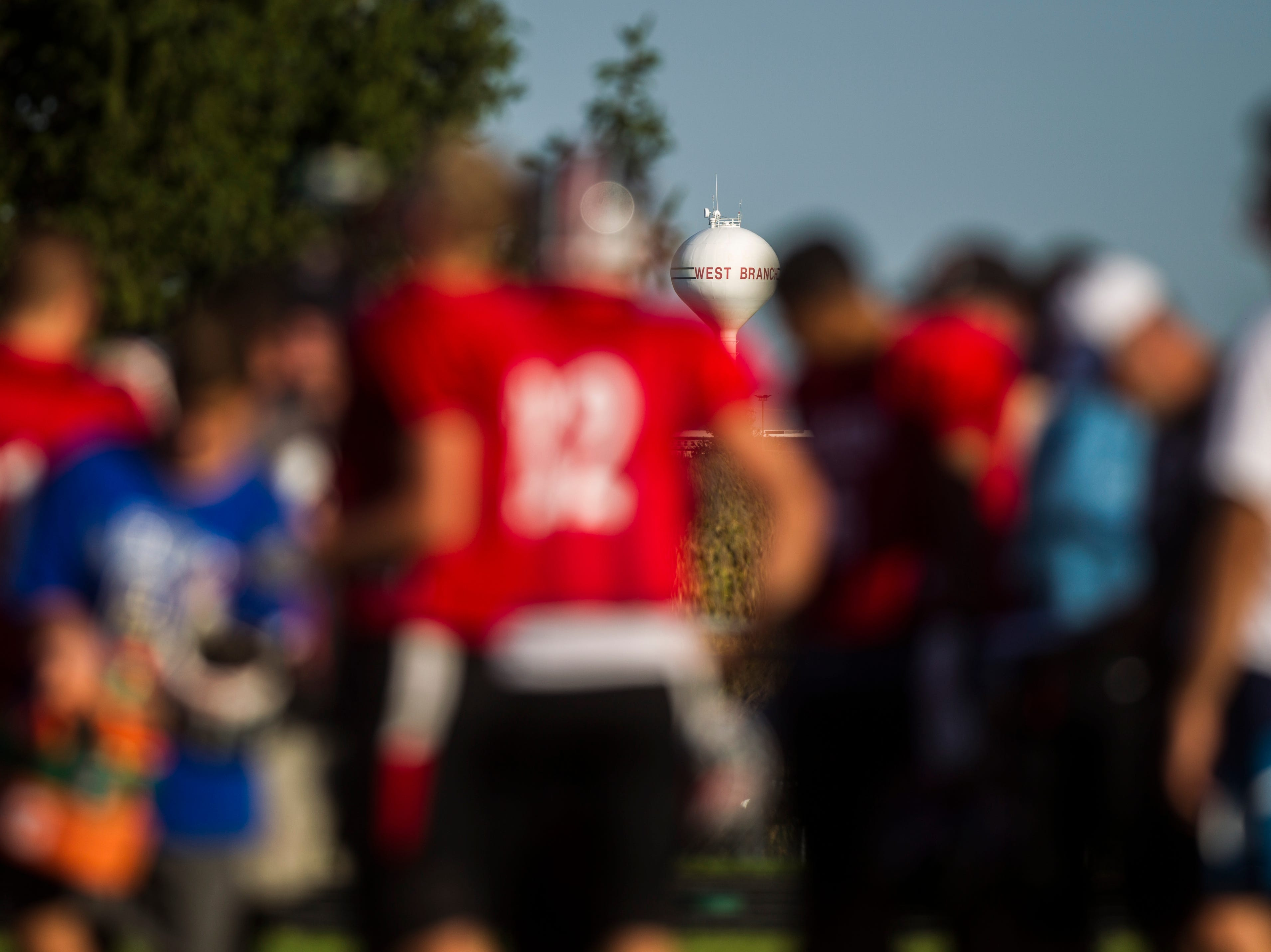 A West Branch water tower along Interstate 80 is seen between players during a varsity football practice on Tuesday, Sept. 11, 2018, at the West Branch High School practice field.
