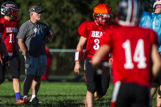 West Branch football head coach Butch Pedersen calls out instructions to players during a varsity football practice on Tuesday, Sept. 11, 2018, at the West Branch High School practice field.