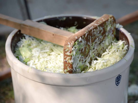An implement used to pound shredded cabbage rests atop the large crock during the process to make sauerkraut at St. Joseph Catholic Church in Gluckstadt.