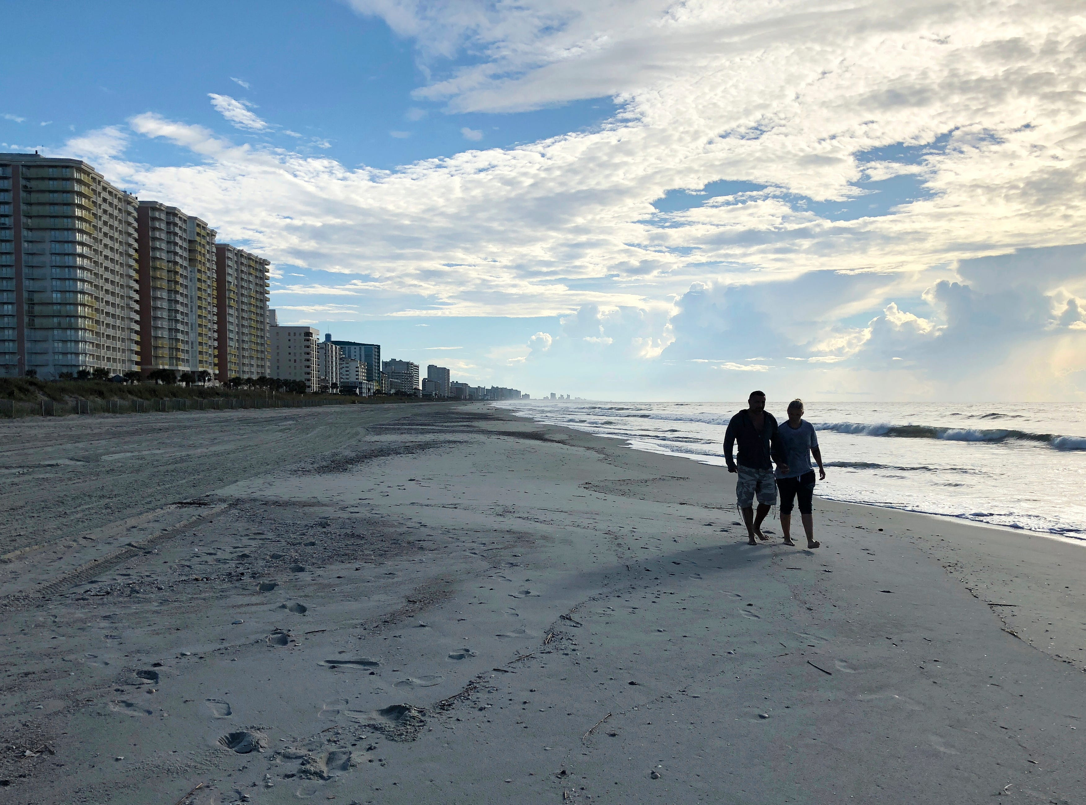 Chris and Nicole Roland walk down a beach in North Myrtle Beach, S.C. on Wednesday, Sept. 12, 2018. The couple boarded up their uncle's condominium and are leaving soon as Hurricane Florence approaches.