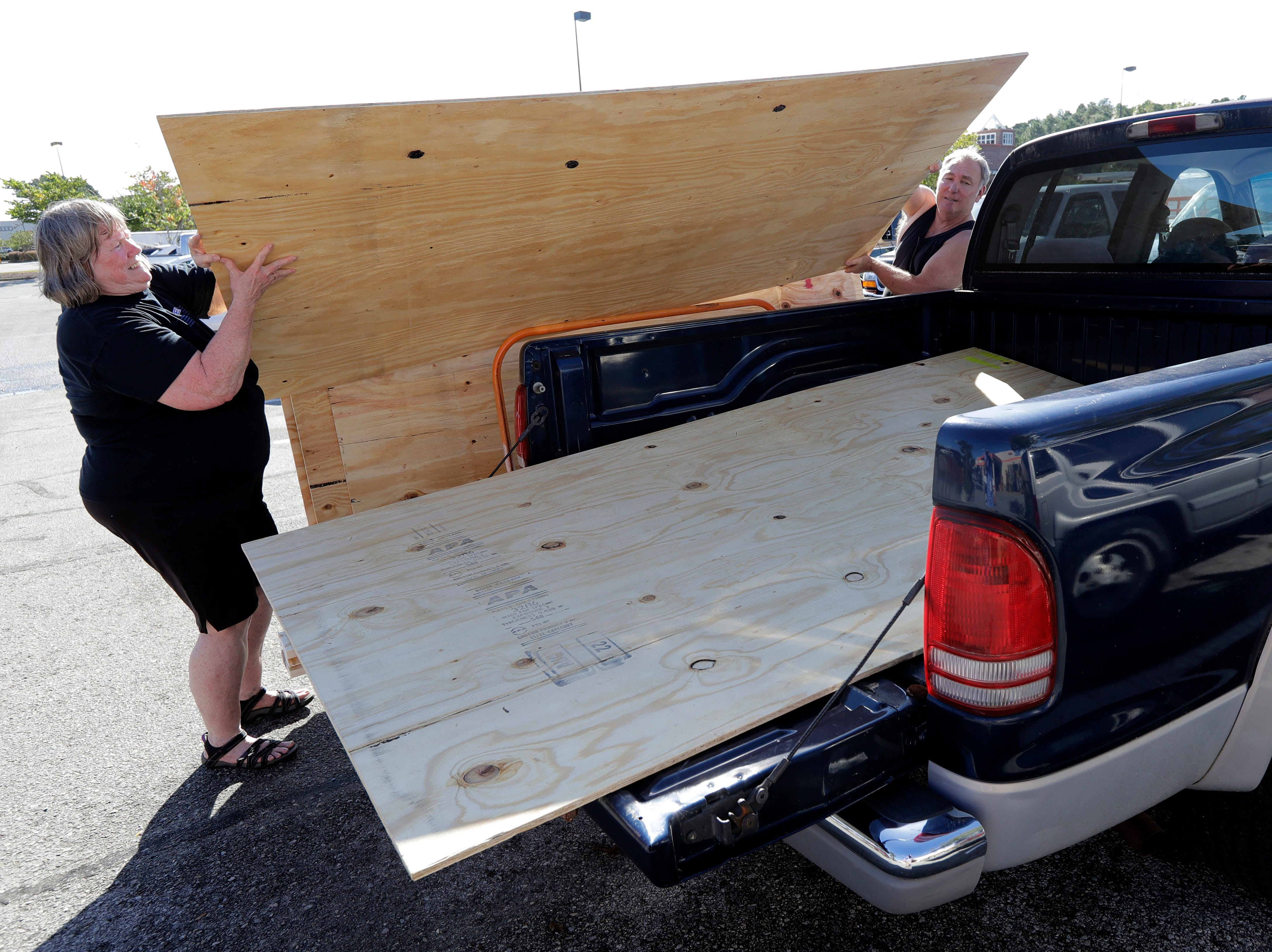 Mickey Manes, right, and Diane Manes, left, load plywood into their truck in advance of Hurricane Florence in Wilmington, N.C., Wednesday, Sept. 12, 2018. Florence exploded into a potentially catastrophic hurricane Monday as it closed in on North and South Carolina, carrying winds up to 140 mph (220 kph) and water that could wreak havoc over a wide stretch of the eastern United States later this week.