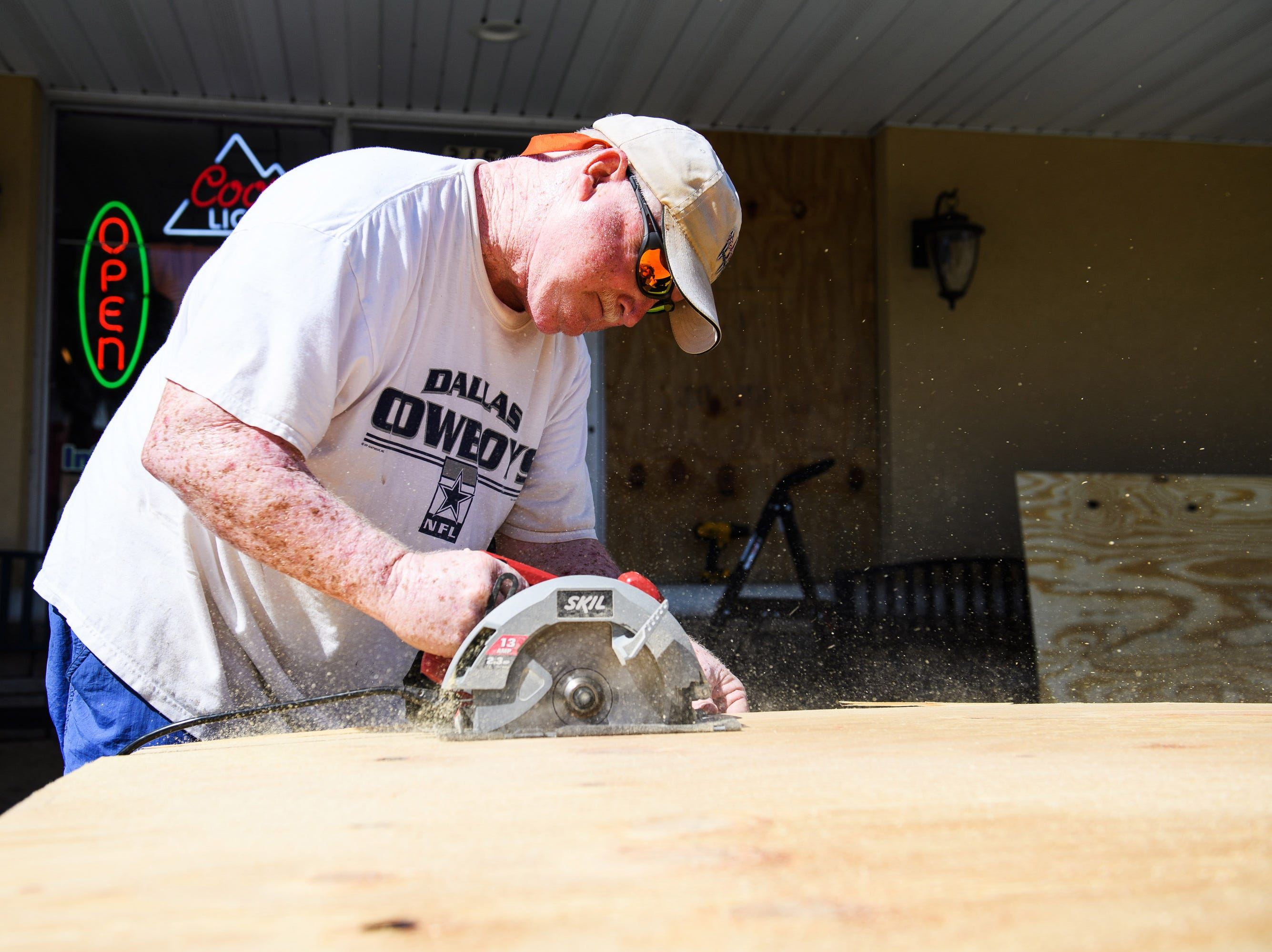 Sept. 11, 2018; North Myrtle Beach, SC, USA; Lee Dorton, owner of Infused Olive in North Myrtle Beach, cuts pieces of plywood before placing them over the windows of his business on Tuesday, Sept. 11, 2018.