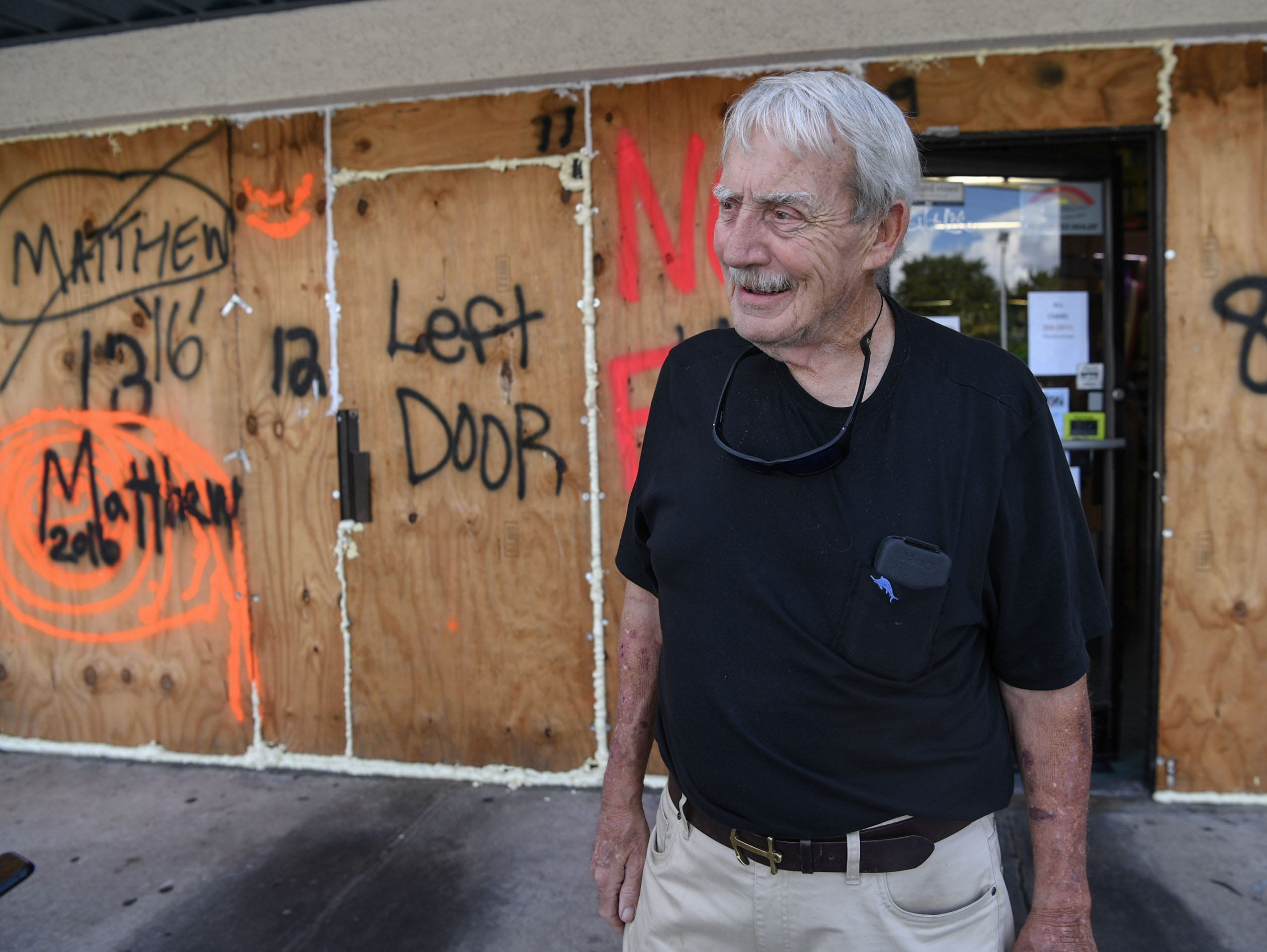 Sep 11, 2018; Wilmington, NC, USA; Plywood boards cover windows at Redix store at Wrightsville Beach on Tuesday, September 11, 2018. Gordon Reddick, owner of the store has used the same boards since 1993, and wrote names for each storm since then. Hurricane Florence is expected to arrive in Wilmington, North Carolina late Thursday night through Friday morning.