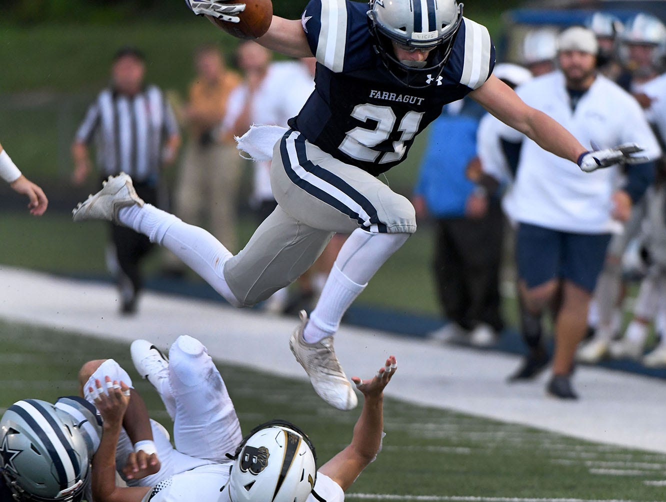 Farragut's Gabe Hensley (21) leaps over a Bradley Central defender during their game Friday, August 17, 2018 at Farragut High School.