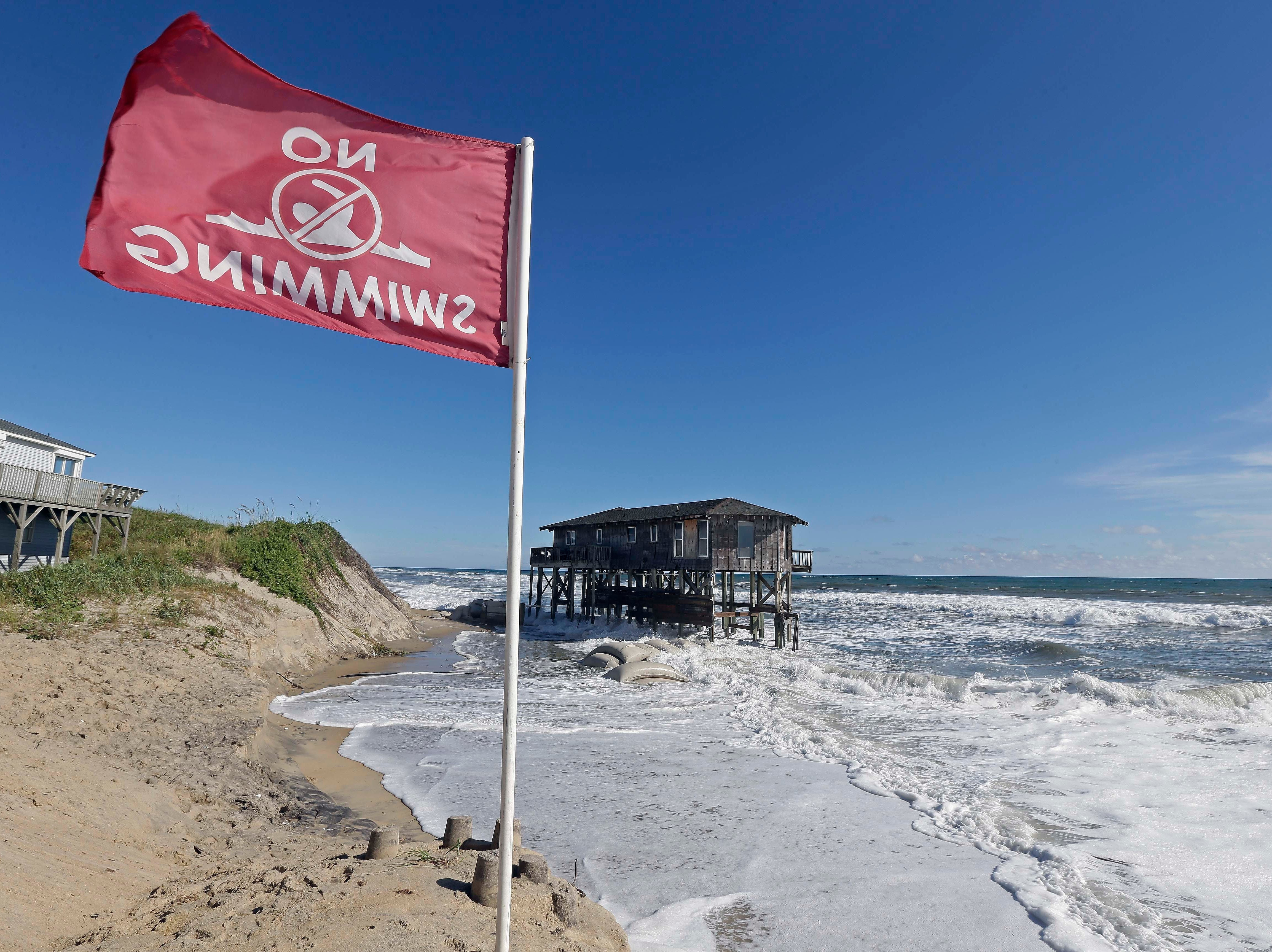 "A warning flag flies as high tide surrounds an old cottage that has already succumbed to long-term beach erosion in Nags Head, N.C., Wednesday, Sept. 12, 2018 as Hurricane Florence approaches the coast of the Carolinas. The National Weather Service says Hurricane Florence ""will likely be the storm of a lifetime for portions of the Carolina coast."""