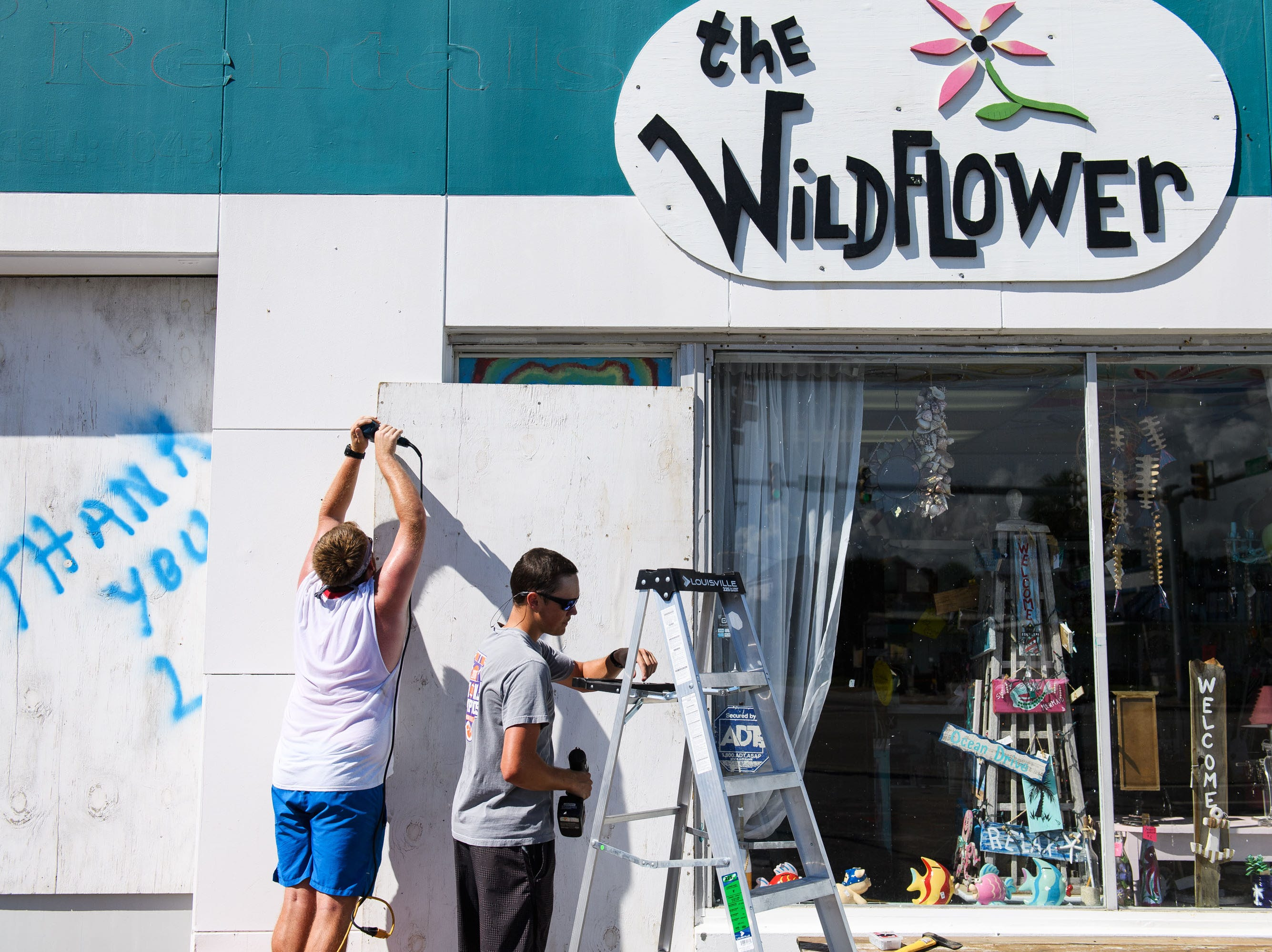 Sept. 11, 2018; North Myrtle Beach, SC, USA; Hunter Cook and Austin Benton board up windows at their grandfather's business, The Wildflower, in North Myrtle Beach on Tuesday, Sept. 11, 2018.