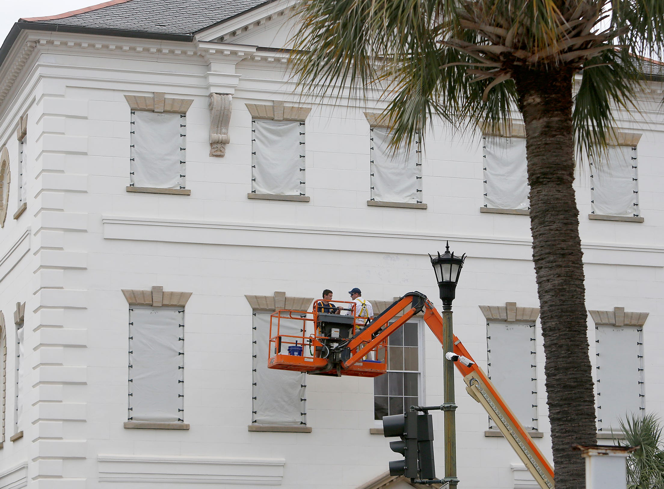 Workers cover the windows of the historic Charleston County Courthouse in Charleston, S.C., in preparation for the advancing Hurricane Florence Tuesday, Sept. 11, 2018.