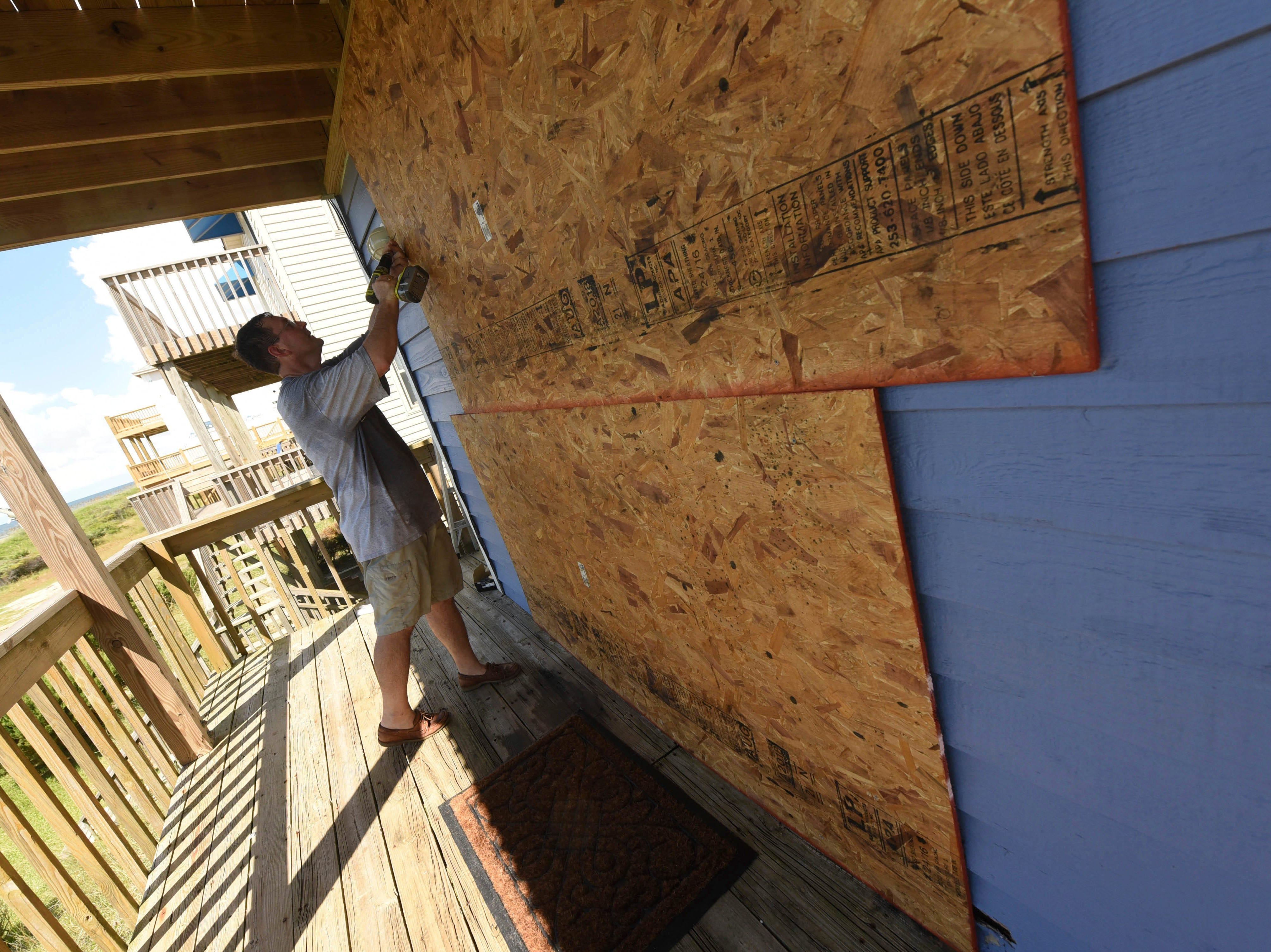 Mark Mead boards up his rental property in Oak Island, N.C., Tuesday Sept. 11, 2018, in preparation for Hurricane Florence.