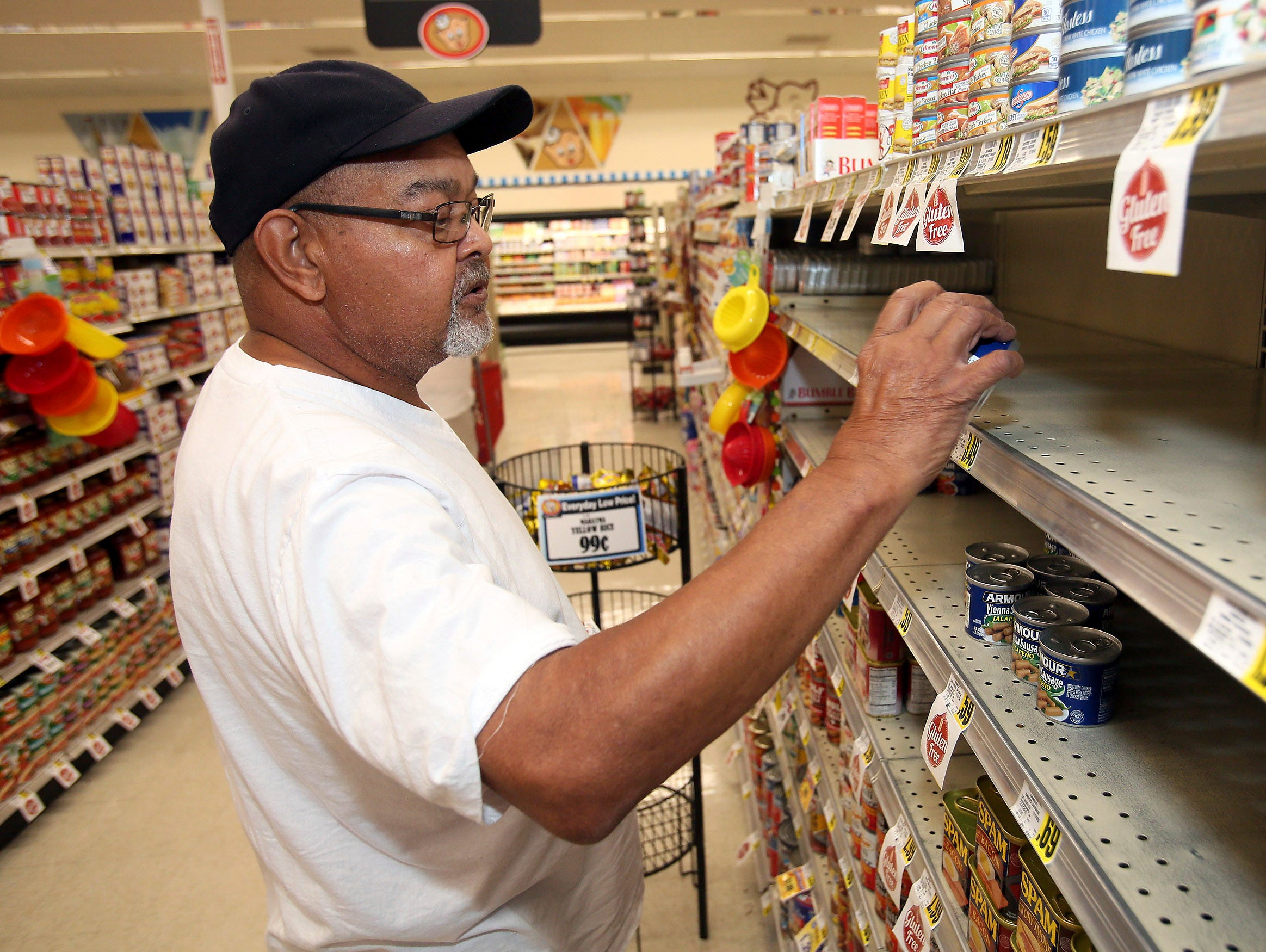 Larry Lynch selects a can of Armour Vienna Bites while grocery shopping in preparation for Hurricane Florence on Tuesday, Sept. 11, 2018, at the Piggly Wiggly store on West Thomas Street in Rocky Mount, N.C.