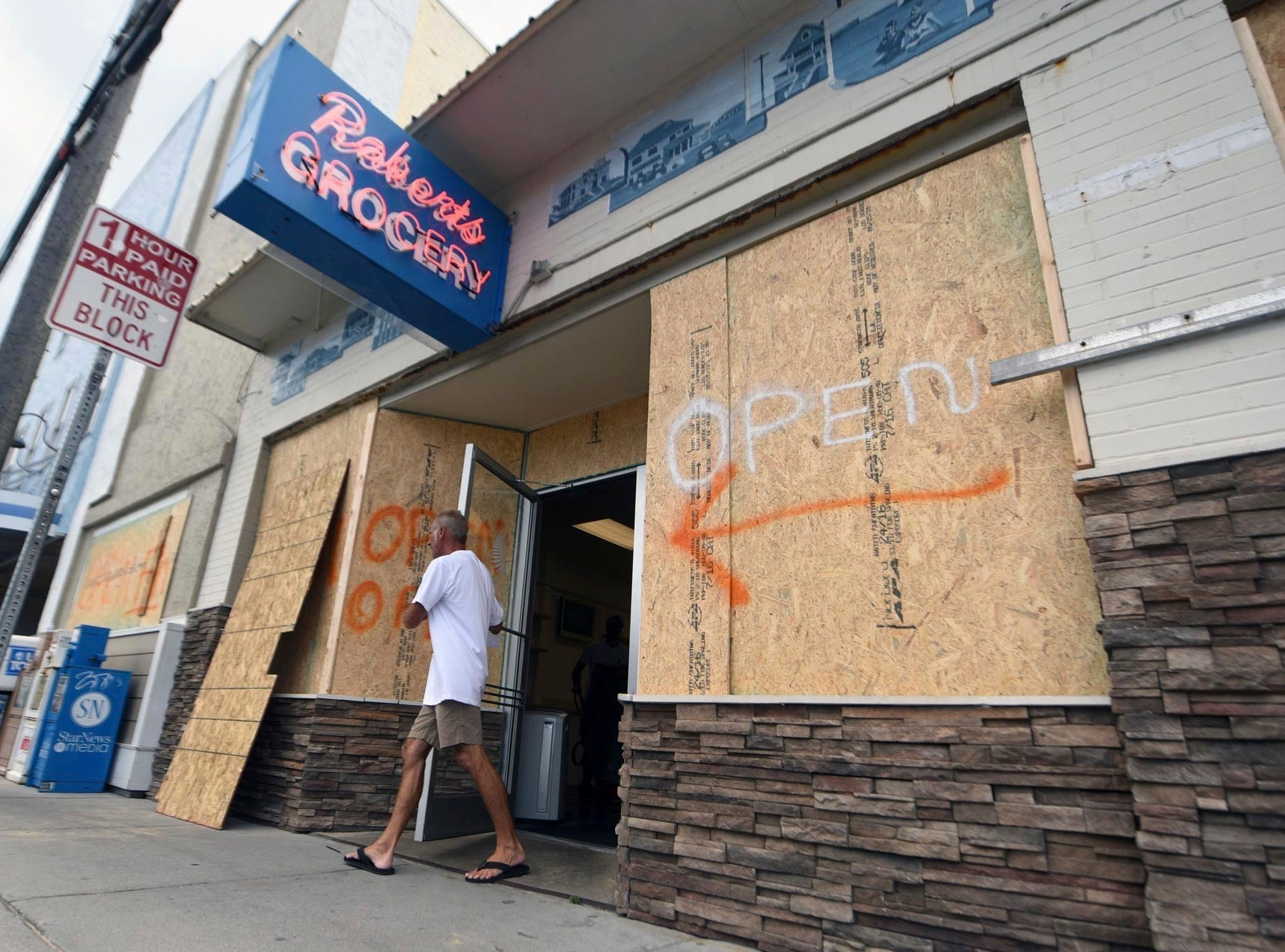 Aman walks out of the boarded up Robert's Grocery in Wrightsville Beach, N.C., in preparation for Hurricane Florence on Tuesday, Sept. 11, 2018.