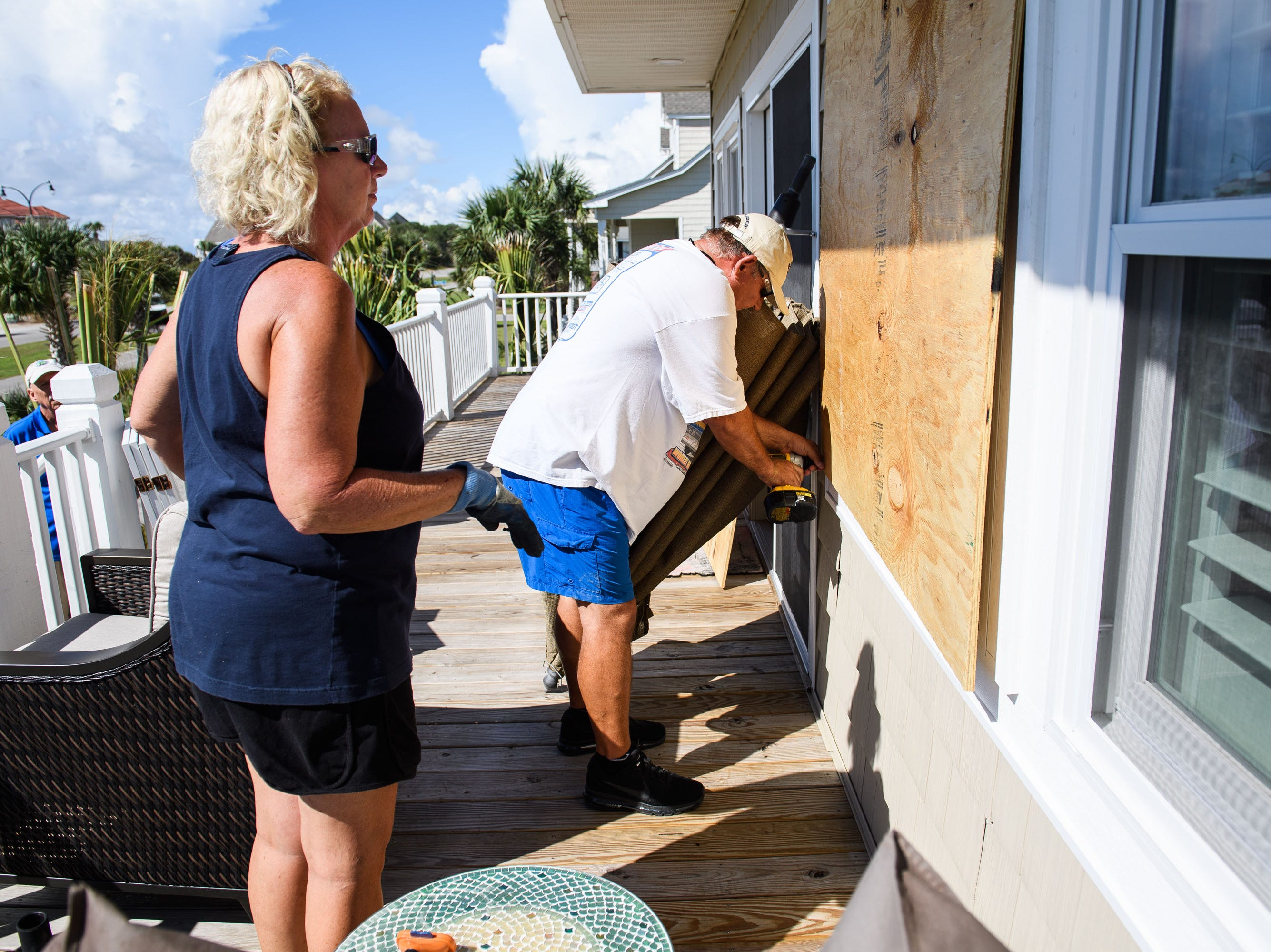 Sept. 11, 2018; North Myrtle Beach, SC, USA; Angie Travis and her husband Jeff place large piece of plywood over a window on their vacation home as they prepare for Hurricane Florence on Tuesday, Sept. 11, 2018.