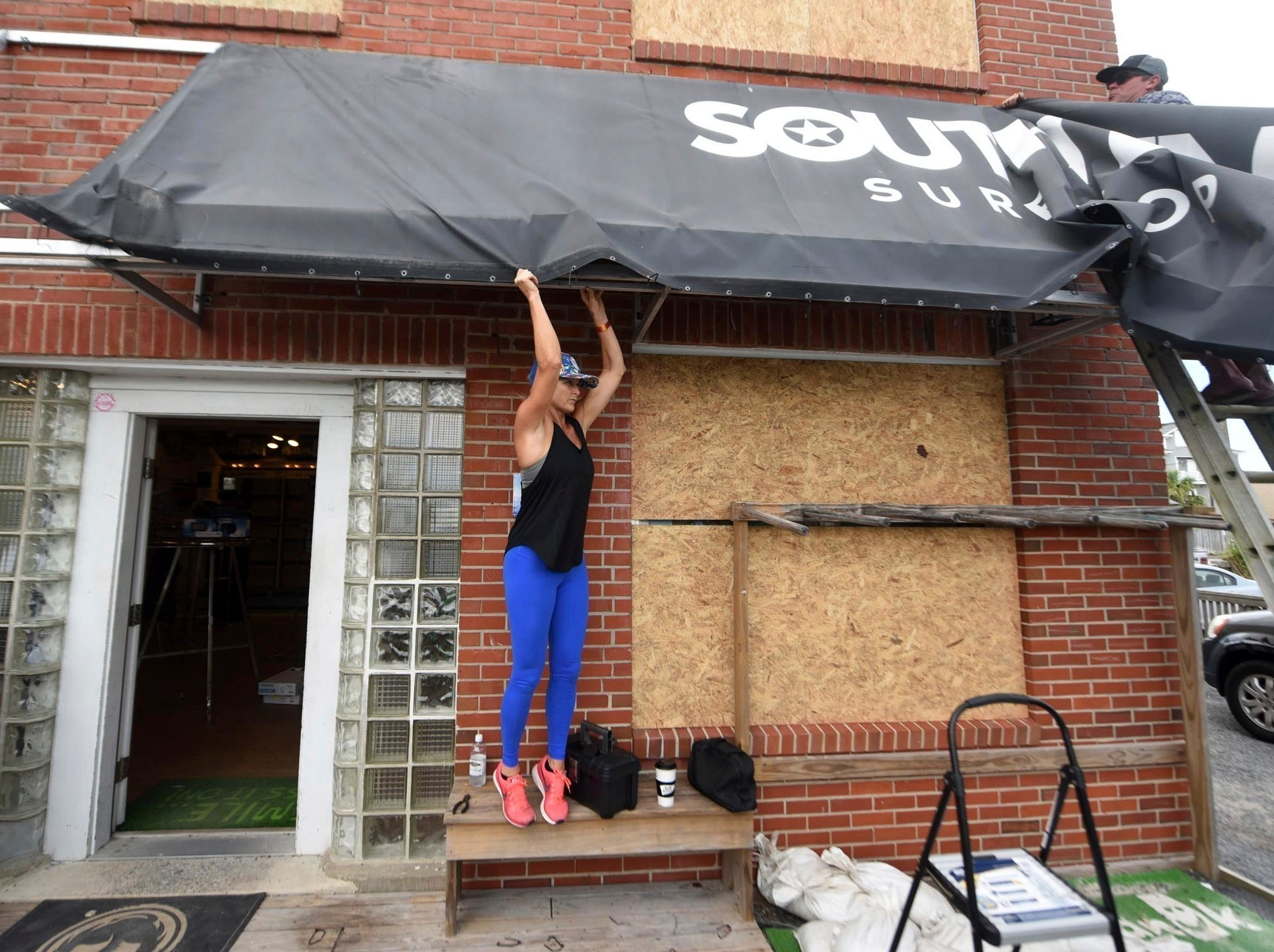 "FILE- In this Sept. 11, 2018, file photo Ashley DeGroote, left, and husband Jeff DeGroote remove the awning at South End Surf Shop in Wrightsville Beach, N.C., in preparation for Hurricane Florence. Though it's far from clear how much economic havoc Hurricane Florence will inflict on the southeastern coast, from South Carolina through Virginia, the damage won't be easily or quickly overcome. In those states, critically important industries like tourism and agriculture are sure to suffer. ""These storms can be very disruptive to regional economies, and it takes time for them to recover,"" said Ryan Sweet, an economist at Moody's Analytics."