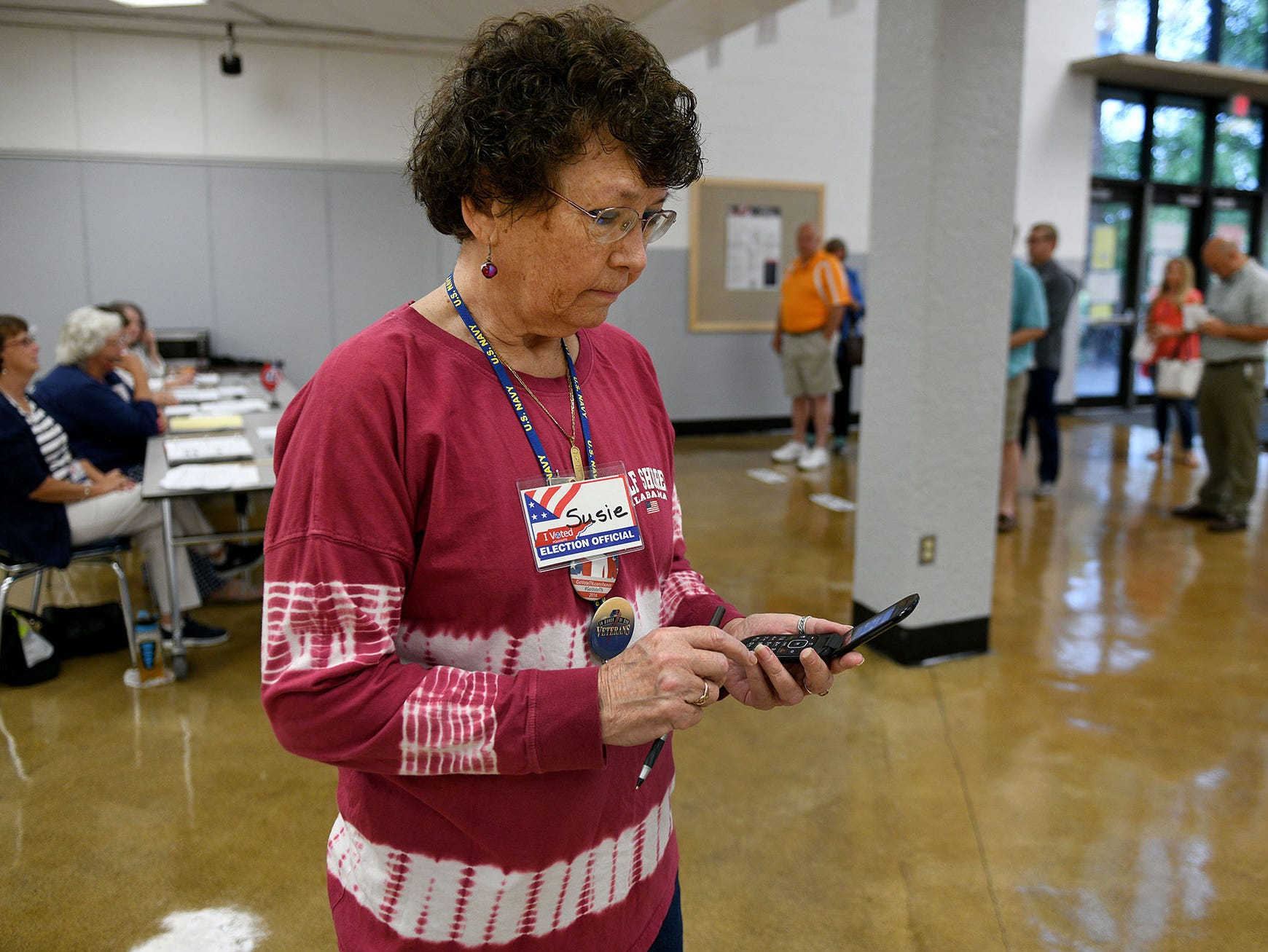Farragut South election official Susie Cataldi watches the clock on her flip-phone to officially open the polls on election day in Knox County Thursday, August 2, 2018.