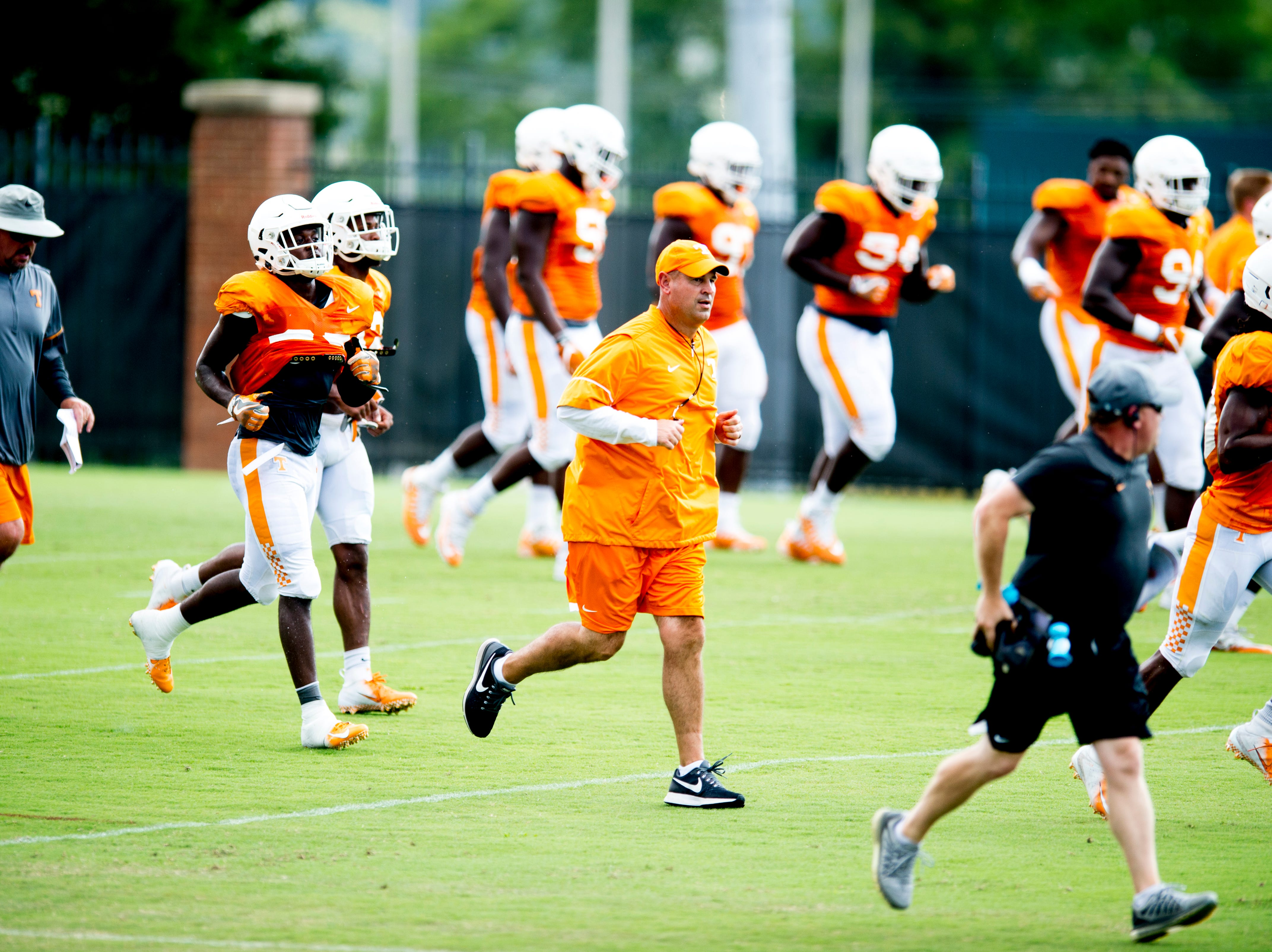 Tennessee Head Coach Jeremy Pruitt runs with players on the field during Tennessee fall football practice at Haslam Field in Knoxville, Tennessee on Wednesday, September 12, 2018.