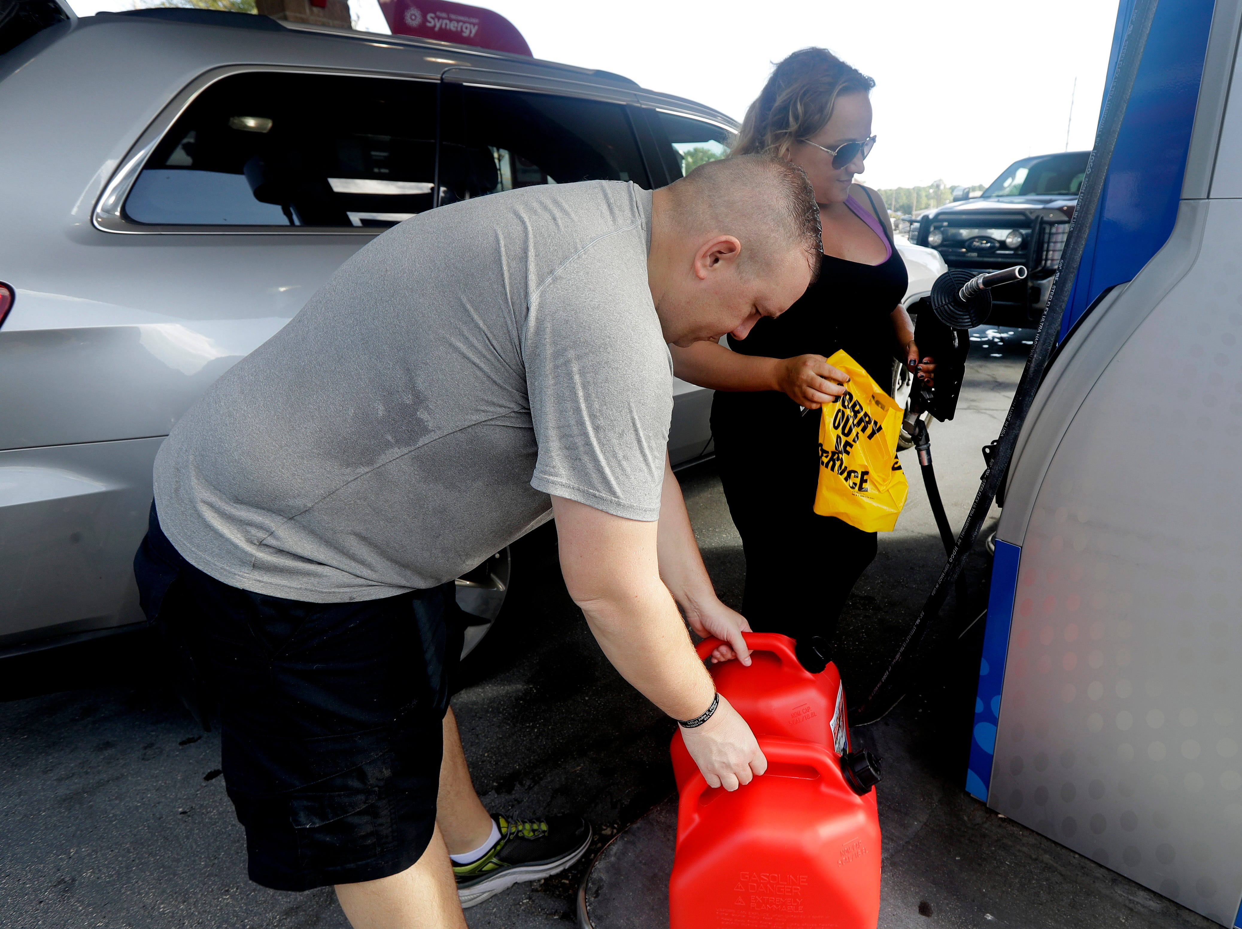 "Sarah Dankanich, right, removes an ""out of service"" wrapper from a gas pump as her husband, Bryan Dankanich, left, prepares to pump gas in cans in advance of Hurricane Florence in Wilmington, N.C., Wednesday, Sept. 12, 2018. Florence exploded into a potentially catastrophic hurricane Monday as it closed in on North and South Carolina, carrying winds up to 140 mph (220 kph) and water that could wreak havoc over a wide stretch of the eastern United States later this week."