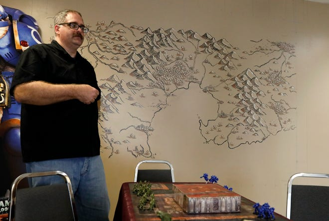 Doug Friess stands in front of a hand painted map of a world he's created with other players as part of a years long Dungeons and Dragons campaign. Friess recently opened a game store called Odyssey Games on North Columbus Street in Lancaster.