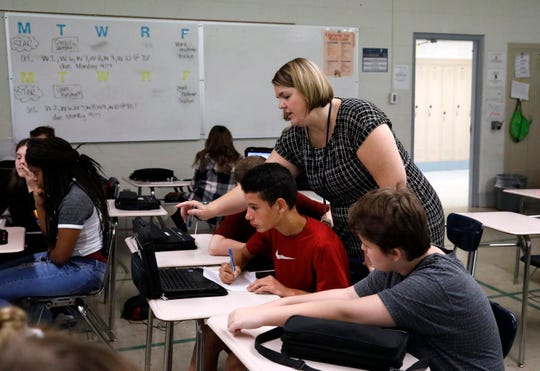 Amanda Kolbe, a math teacher at Thomas Ewing Junior High, talks to students as they work on an in-class assignment Wednesday morning, Sept. 12, 2018, in Lancaster.