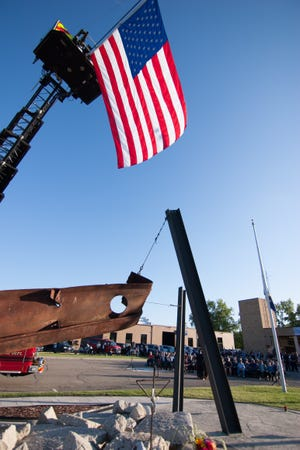 The American flag hangs from a ladder truck over the 9/11 Memorial as a ceremony is held at Brighton Area Fire Authority's Station 31 Tuesday, Sept. 11, 2018.