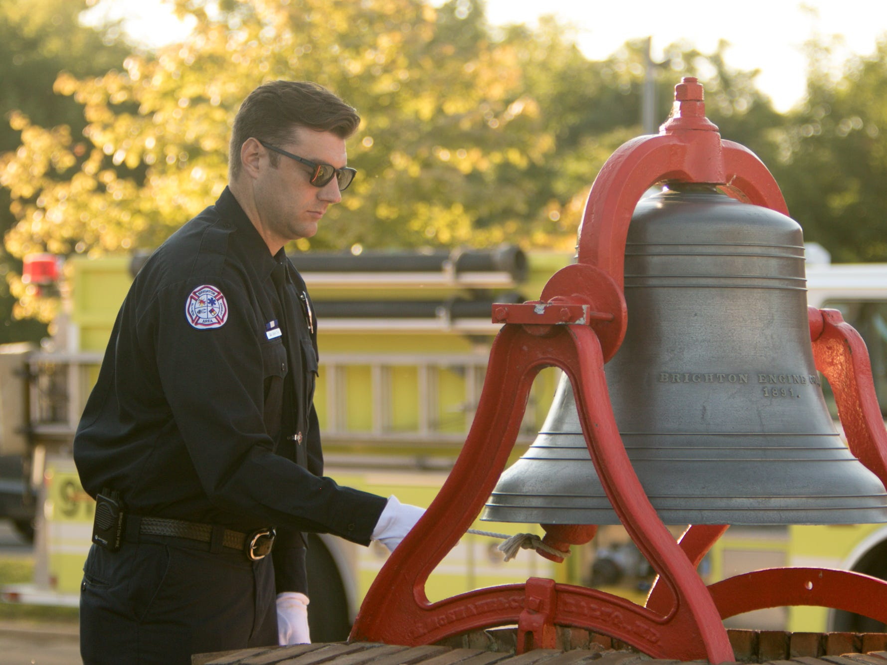 Brighton Area Fire Authority firefighter Ian Griffith rings a bell during the 9/11 memorial ceremony held at Station 31 Tuesday, Sept. 11, 2018.