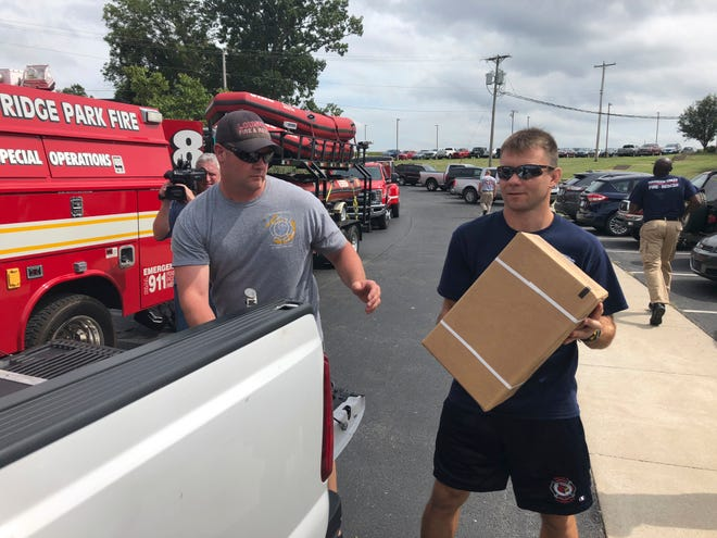 Troy Williams, left, and Sasa Petkovic of the Louisville Fire Department load supplies into a pickup truck in Frankfort, Kentucky, on Wednesday, Sept. 12, 2018. About two dozen Kentucky firefighters are traveling to North Carolina to help with relief efforts for Hurricane Florence.  (AP Photo/Adam Beam)