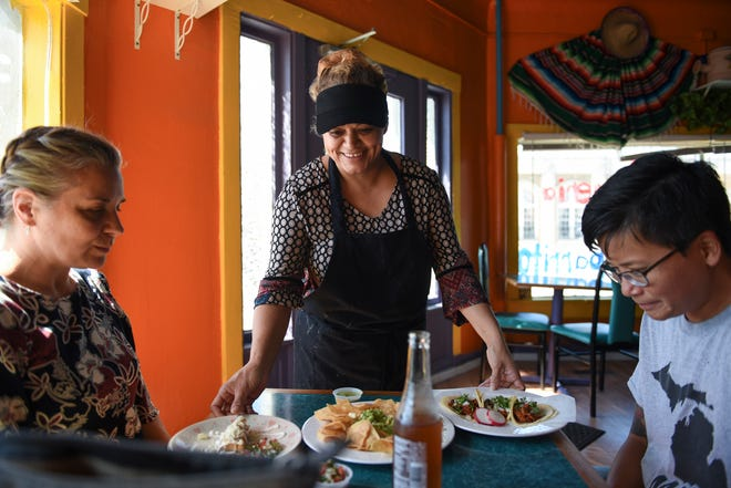 Taqueria El Chaparrito owner Lourdes Casillas delivers lunch to Kimbirly Rindfleisch, left, and May Jotikapukkana, Wednesday, Sept. 12, 2018.