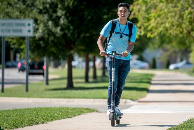 A man rides a Bird scooter along Shaw Lane on Wednesday, Sept. 12, 2018, on the Michigan State University campus in East Lansing. Bird Rides Inc., an electric-scooter sharing service, is now available in East Lansing.