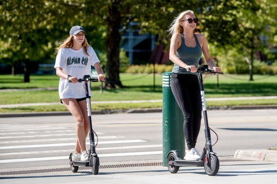 Michigan State University juniors Maddy Coleman, left, and Nina Lombardi ride Bird scooters across Harrison Road near the Kellogg Hotel and Conference Center on Wednesday, Sept. 12, 2018, on the MSU campus in East Lansing. Bird Rides Inc., an electric-scooter sharing service, is now available in East Lansing.