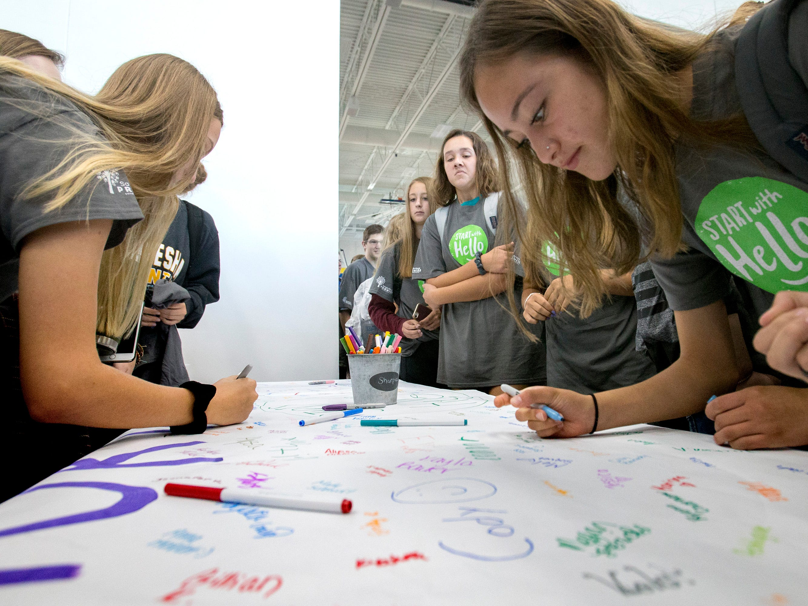 Mukwonago High School students sign a banner following a Sept. 12 all-school assembly to receive the grand prize for the school's Start With Hello program from the Sandy Hook Promise project.