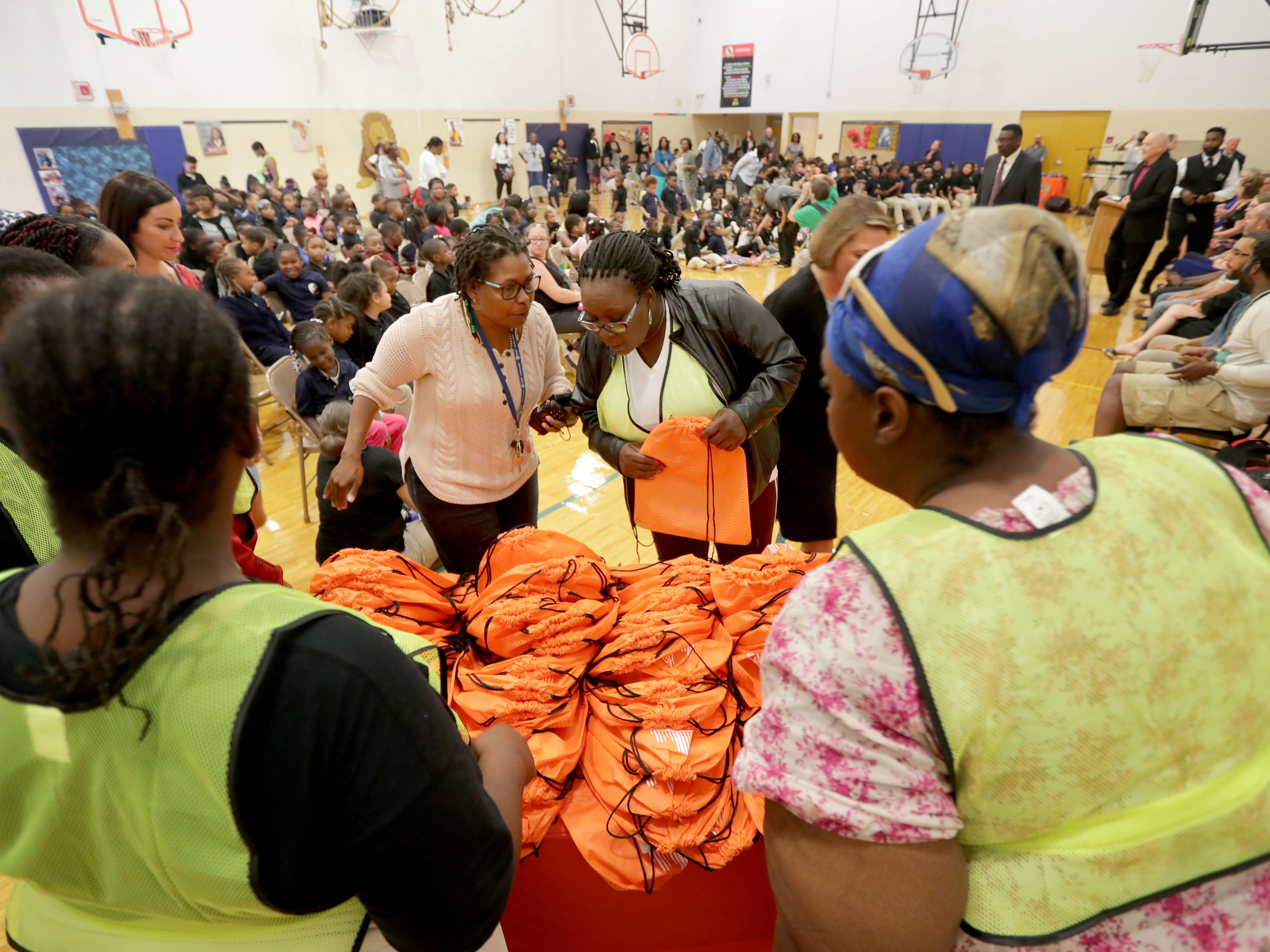 Volunteers organize the backpacks before handing them out.