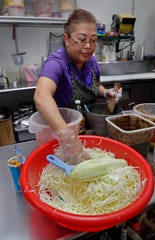 Xay Vang prepares papaya salad using shredded papaya at  Yang's Cafe at Phongsavan Asian Market.