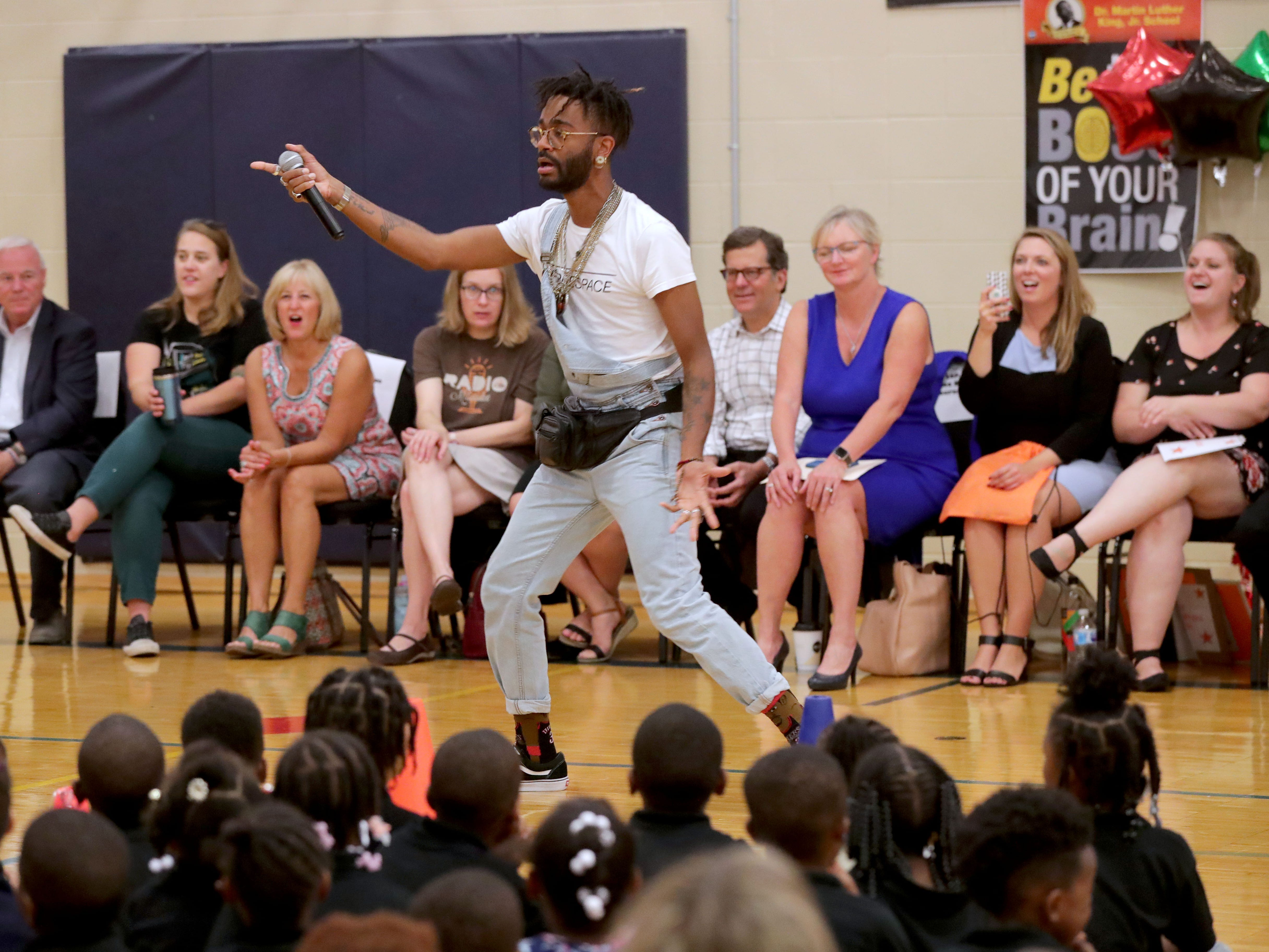 Kellen Abston, the singer and rapper who goes by the stage name Klassik, performs at the assembly before the backpacks were handed out.