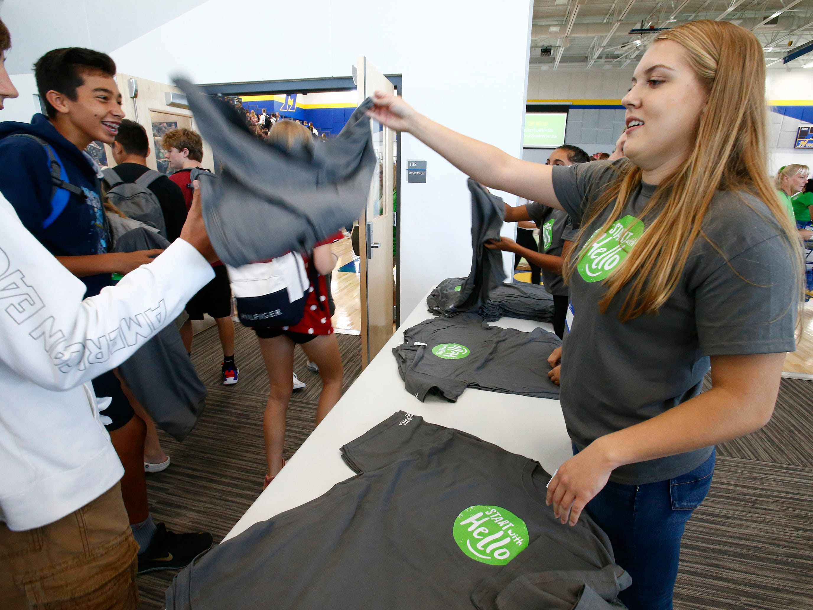 Junior Erica Kudronowicz hands out t-shirts to Mukwonago High School students arriving for a Sept. 12 all-school assembly to receive the grand prize for the school's Start With Hello program from the Sandy Hook Promise project.