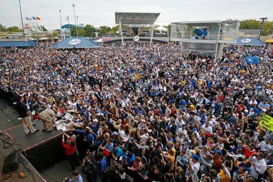 Ryan Braun addresses the crowd as Mike Cameron bends over to sign autographs as thousands of Brewers fans gather at the Miller Oasis on the Summerfest grounds for a pep rally before the team headed to the postseason for the first time since 1982.