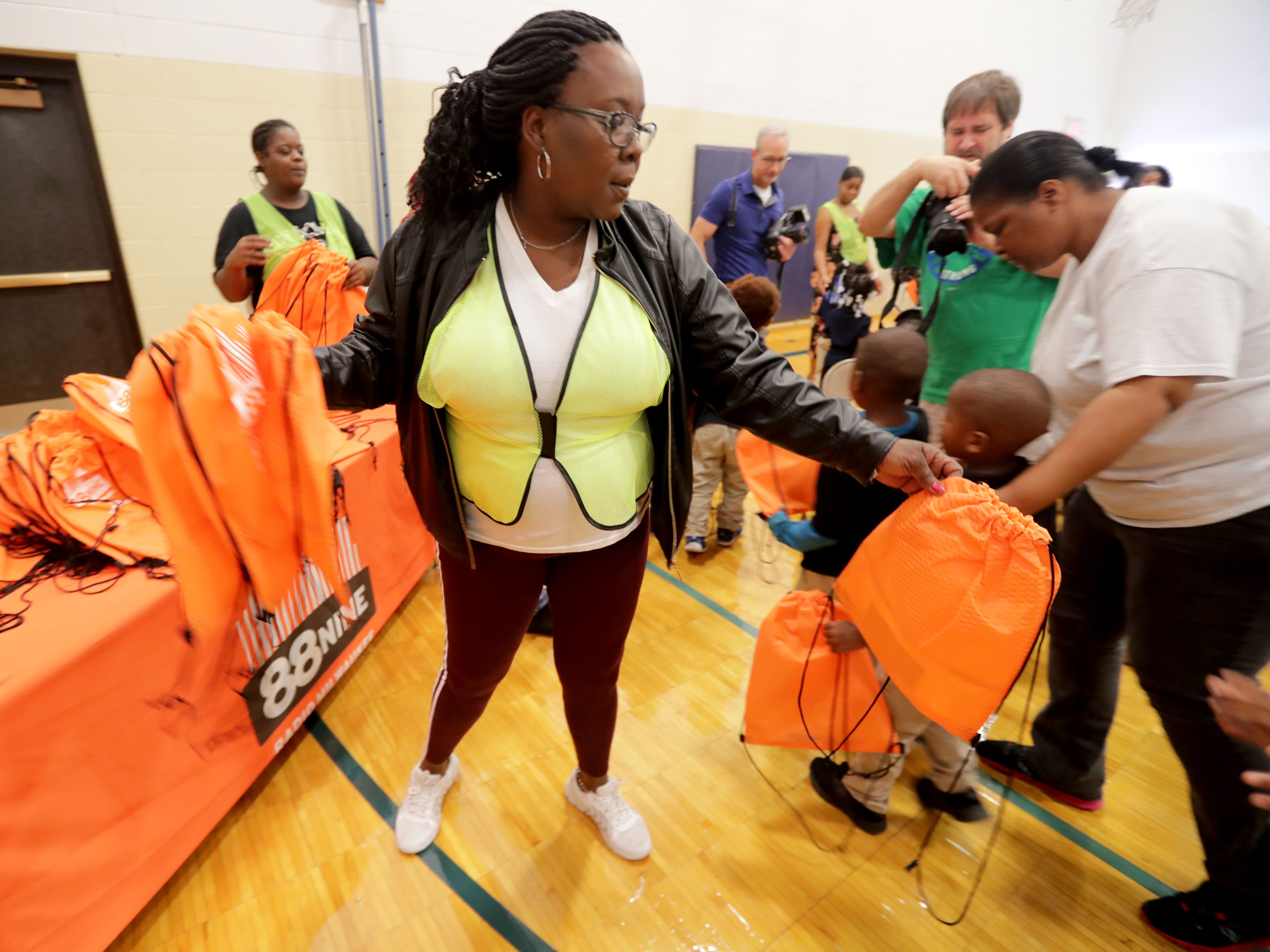 Volunteer Yulene Smith hands out backpacks to students at Dr. Martin Luther King Jr. Elementary School, 3275 N. 3rd St., on Wednesday. The backpacks will be filled with donated school supplies.